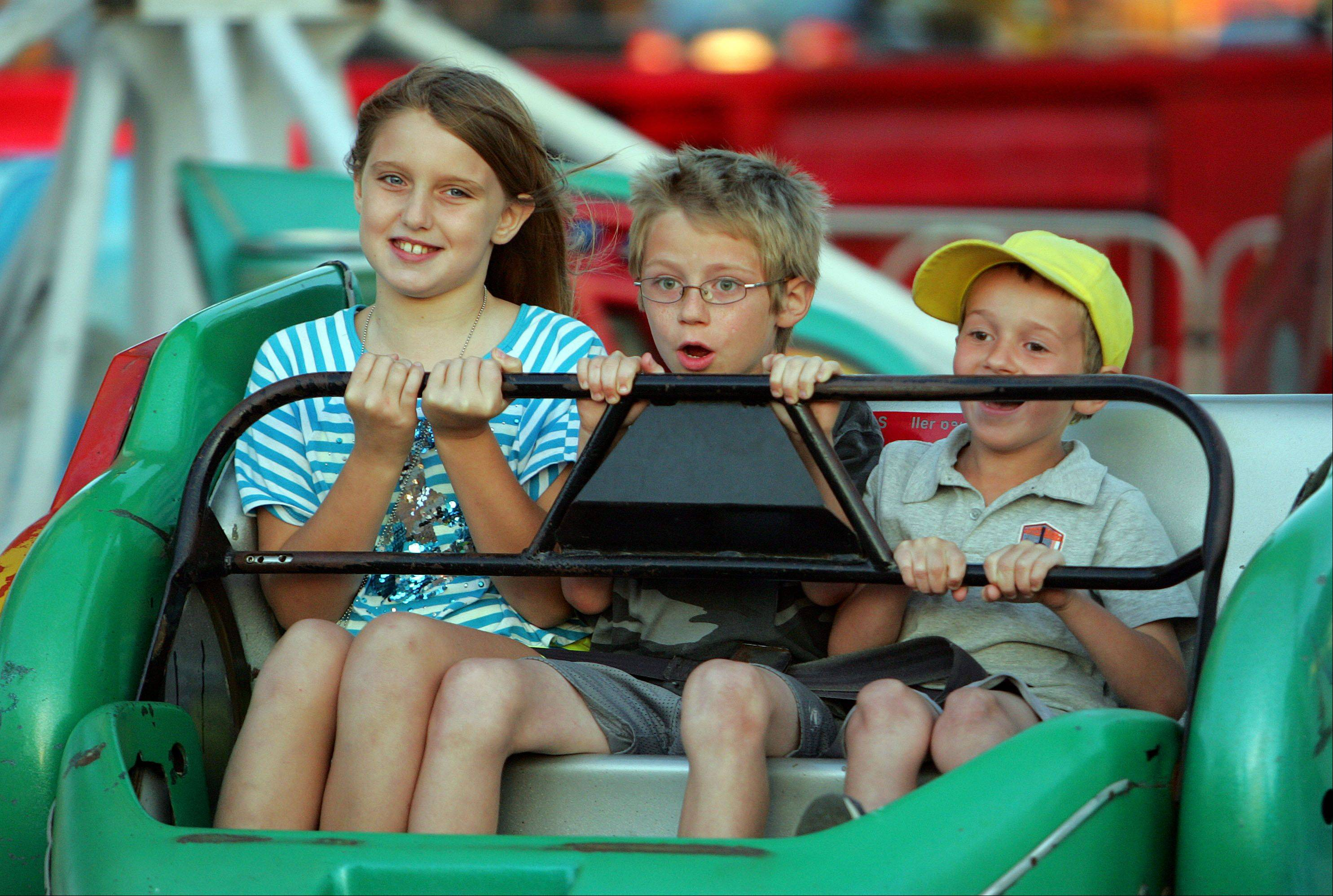 From left, Amelia Cox and Logan and Liam Micheletto, all of Lakemoor, ride a carnival ride during last year's Lakemoor Fest.