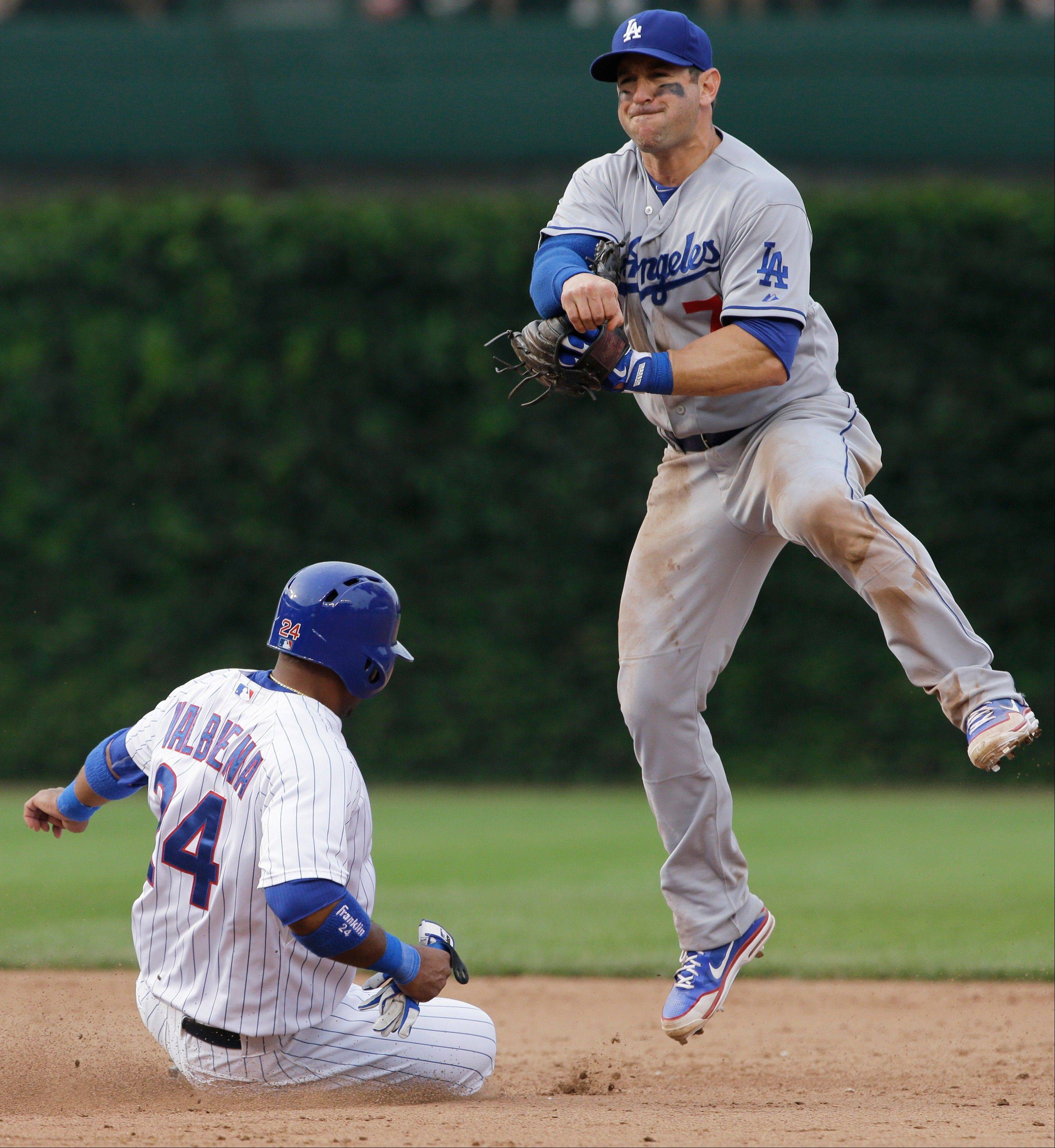Los Angeles Dodgers shortstop Nick Punto, right, looks to the first after forcing out Chicago Cubs' Luis Valbuena, left, during the sixth inning of a baseball game on Friday, Aug. 2, 2013, in Chicago Cubs' David DeJesus was out at first base.