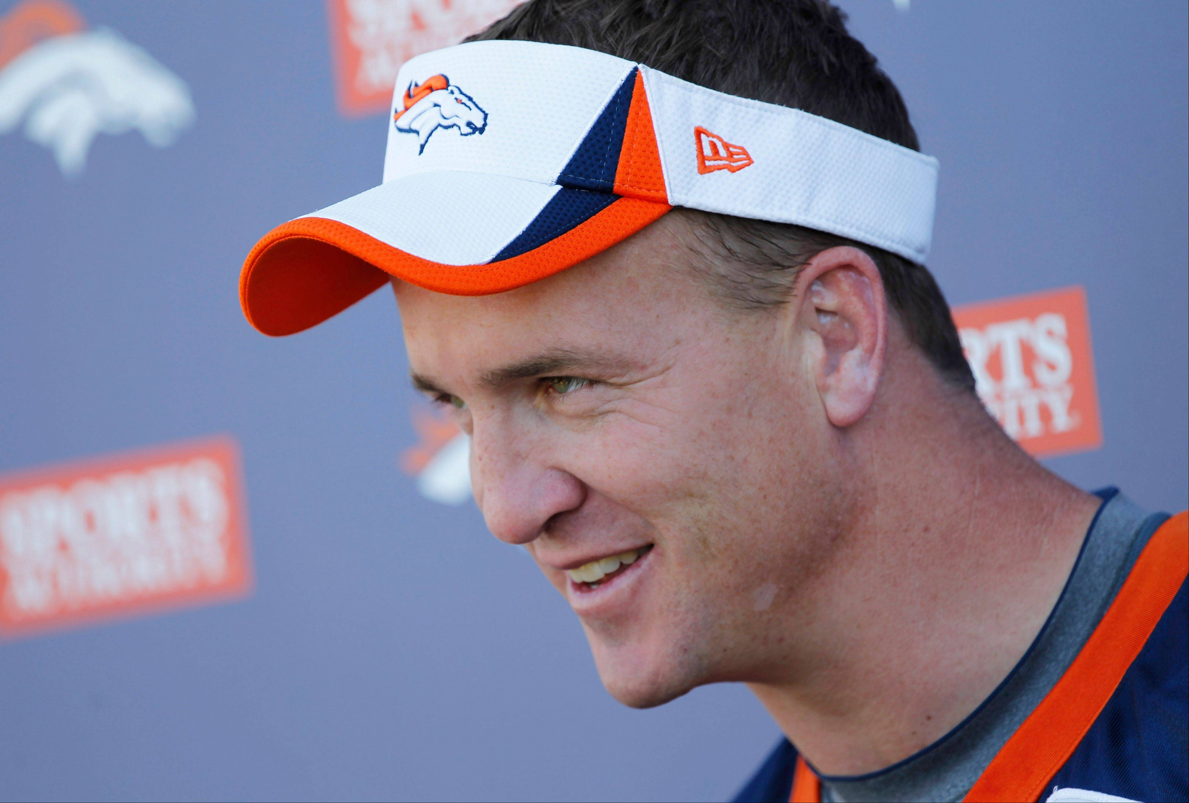 Denver Broncos starting quarterback Peyton Manning jokes with reporters after taking part in the morning session at the team's NFL training camp in Englewood, Colo., on Tuesday, Aug. 6, 2013.