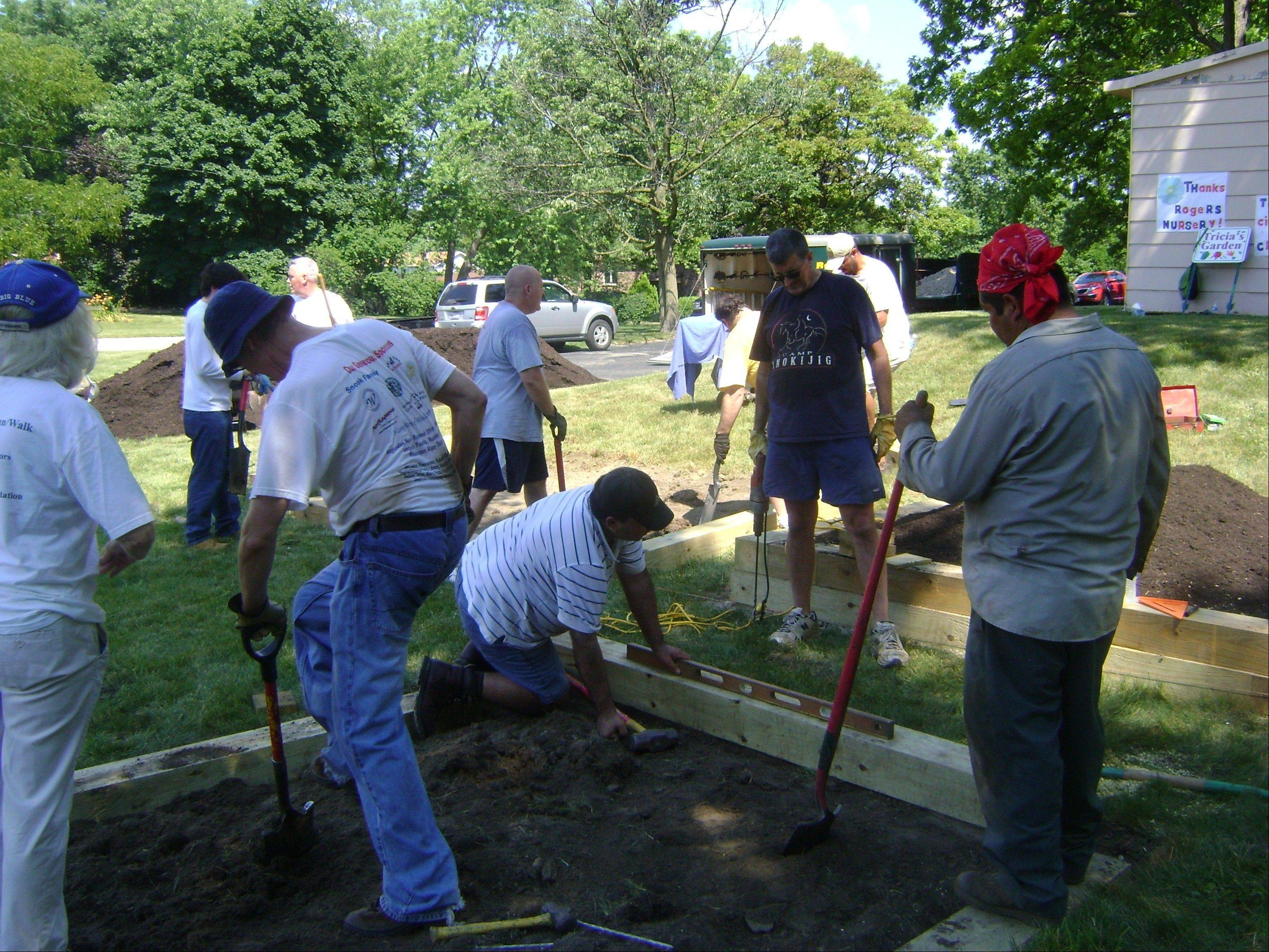Volunteers from Rogers Nursery and the Office of Lake County Clerk of the Circuit Court prepare raised bed gardens.