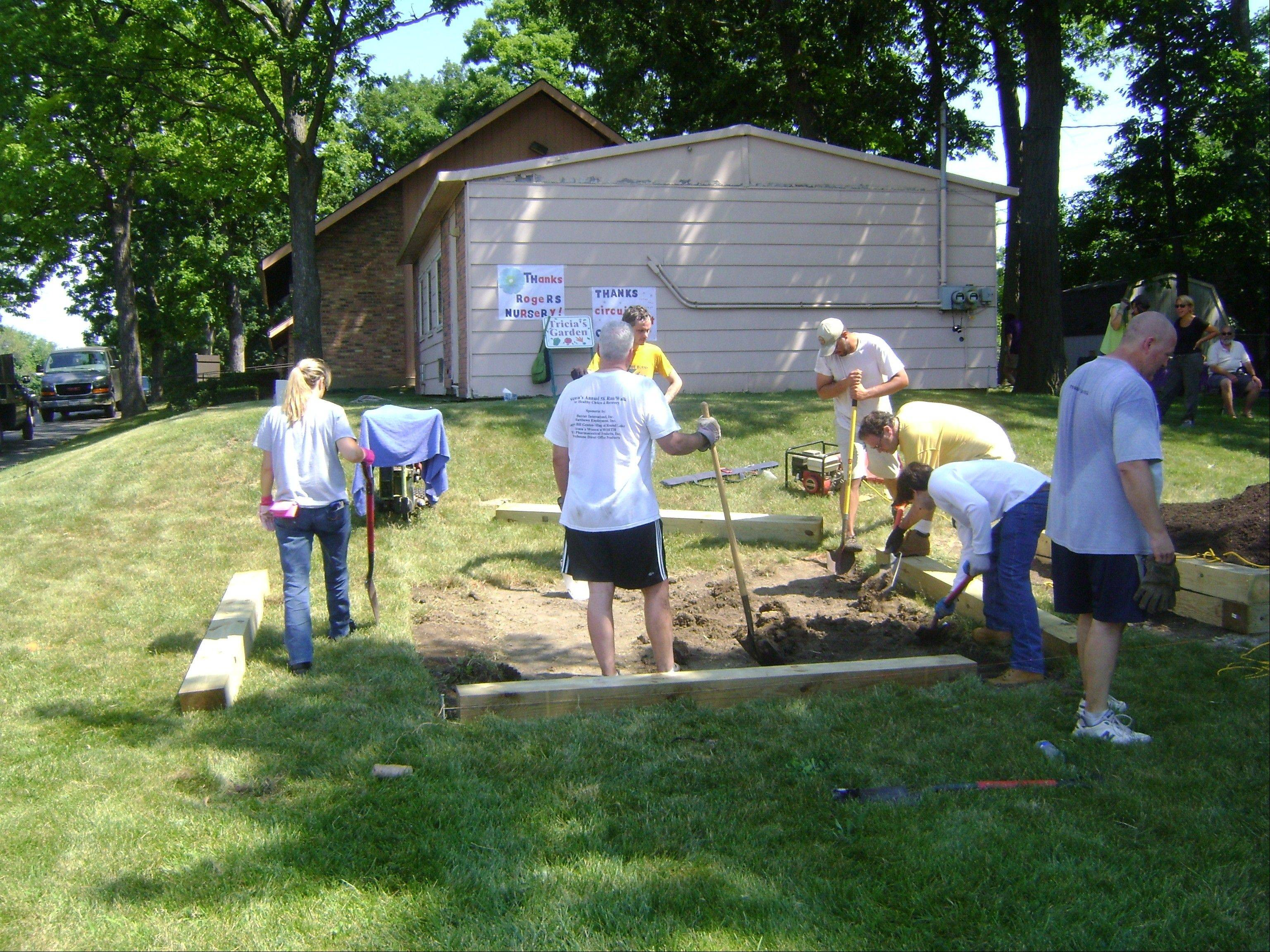Keith Brin, Lake County Clerk of the Circuit Court, and volunteers prepare a raised bed garden.