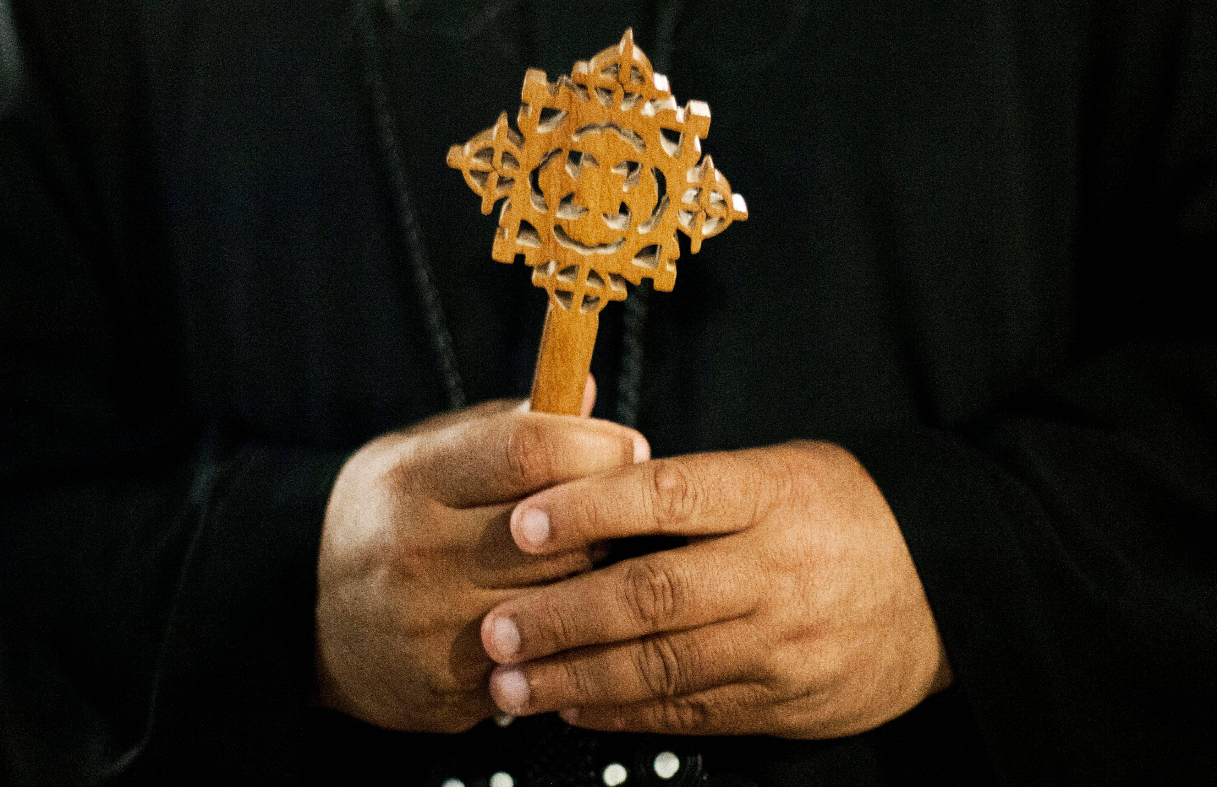 A Coptic Christian monk holds a Coptic cross at Al-Mahraq monastery during the preparation of a religious festival in Assiut, Egypt. Islamists have stepped up a hate campaign against the area's Christians.
