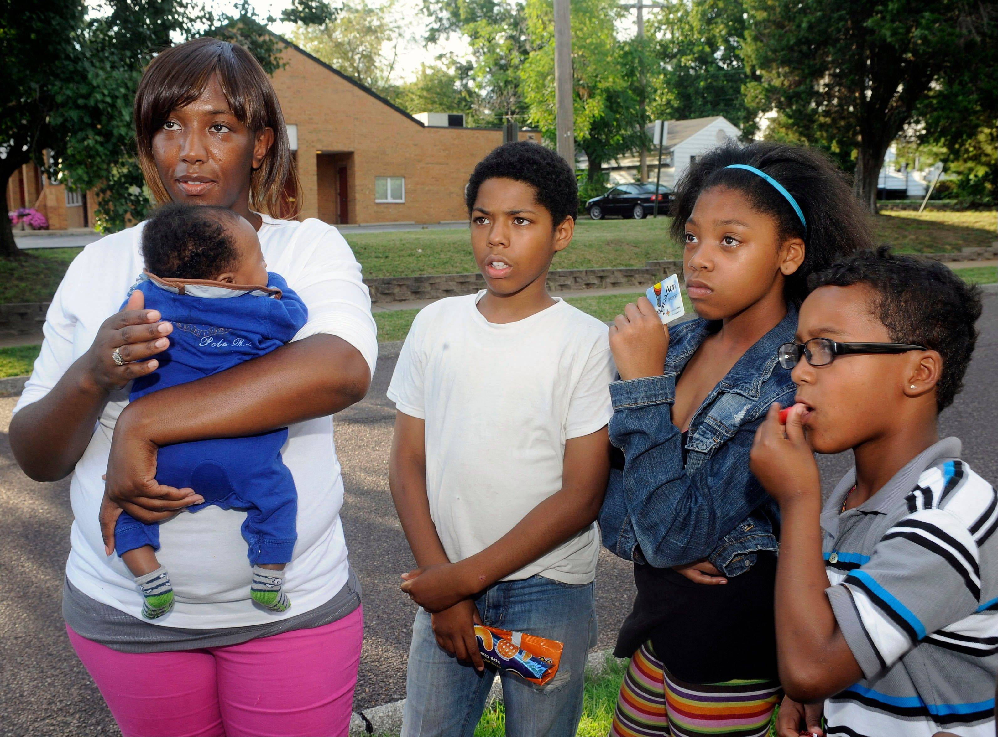 Christina Holmes, left, 29, of the Normandy Schood District in St. Louis County holds her infant Kerian, one month old, as she discusses the school transfer program in Normandy, Mo., standing next to three of her children, left to right, Daevion, 12, Amelian, 10, and Andrew, 8, Wednesday, Aug. 7, 2013. Christina's 14-year-old son will attend school in the Francis Howell School District as part of the transfer program.