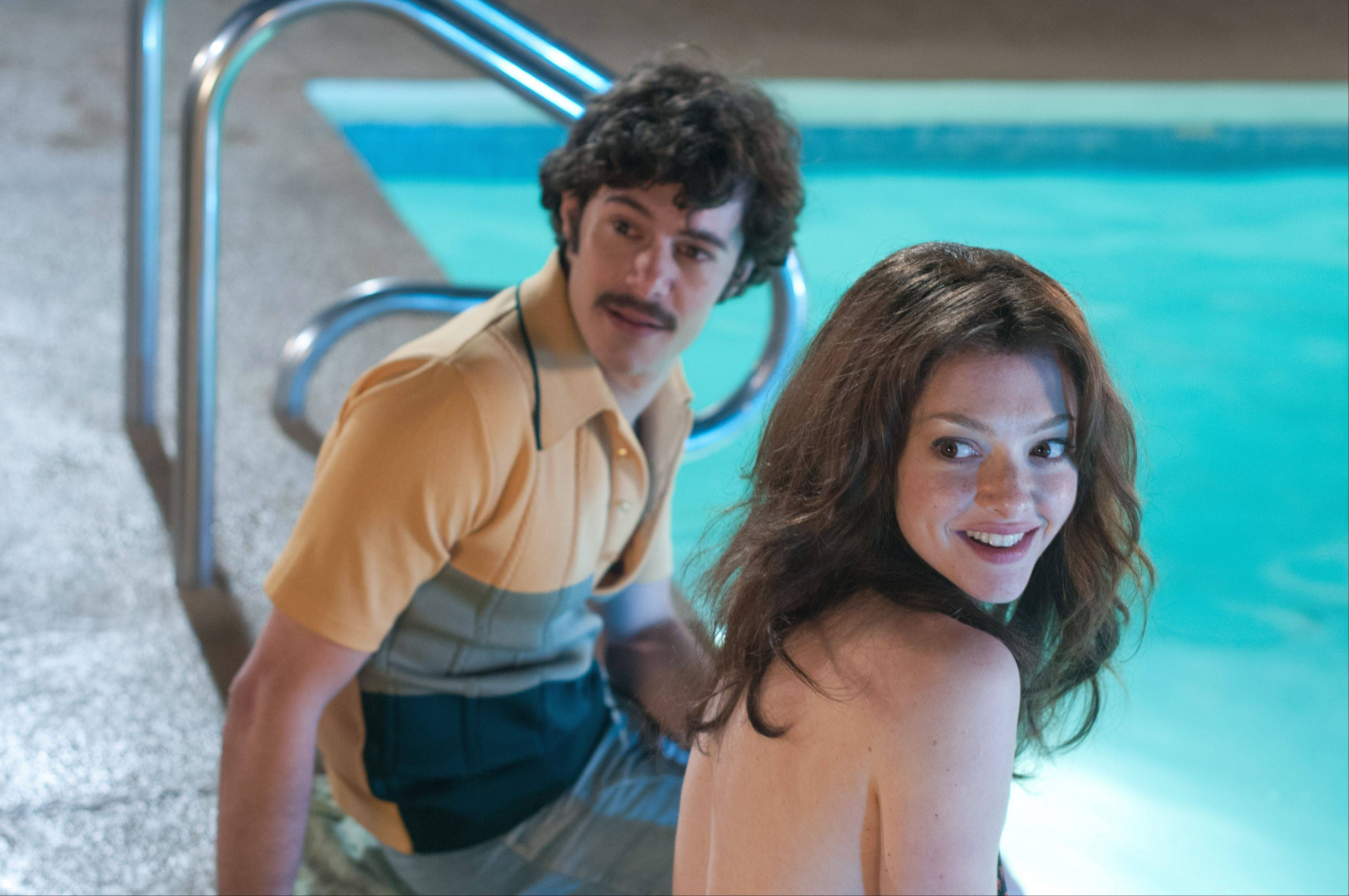 "Adult film star Harry Reems (Adam Brody) prepares for a scene with Linda Boreman (Amanda Seyfried) in the biographical drama ""Lovelace."""