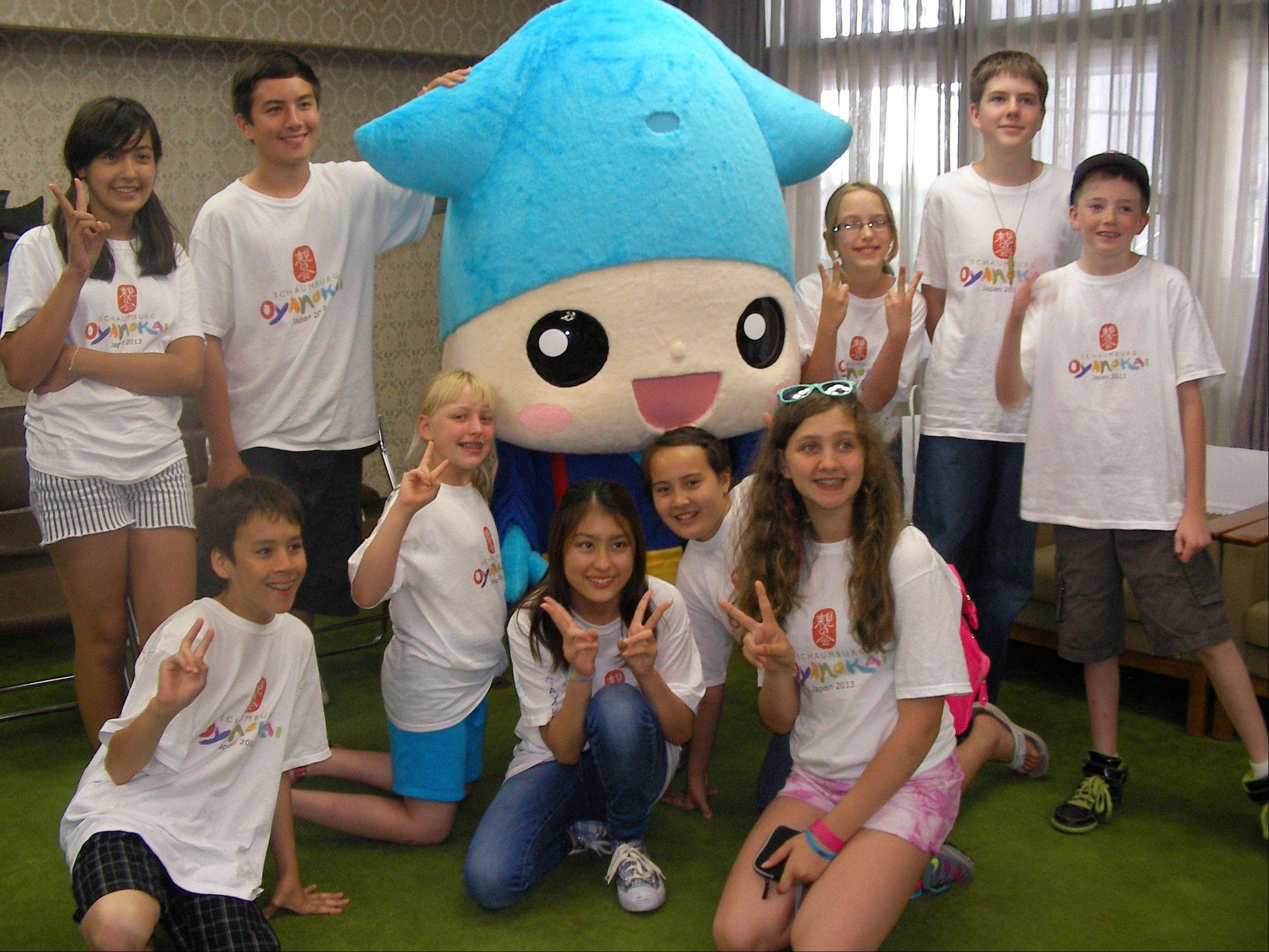 The visiting students pose with Namerikawa's firefly squid mascot, Kirarin.
