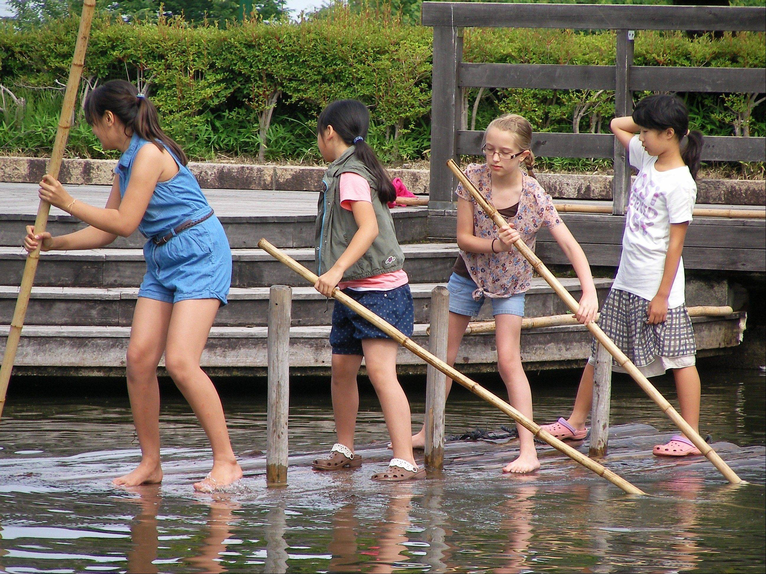 Dooley School students Emma Rogers, left, and Margie Vollkommer, middle, enjoy playing on a raft with Japanese friends.