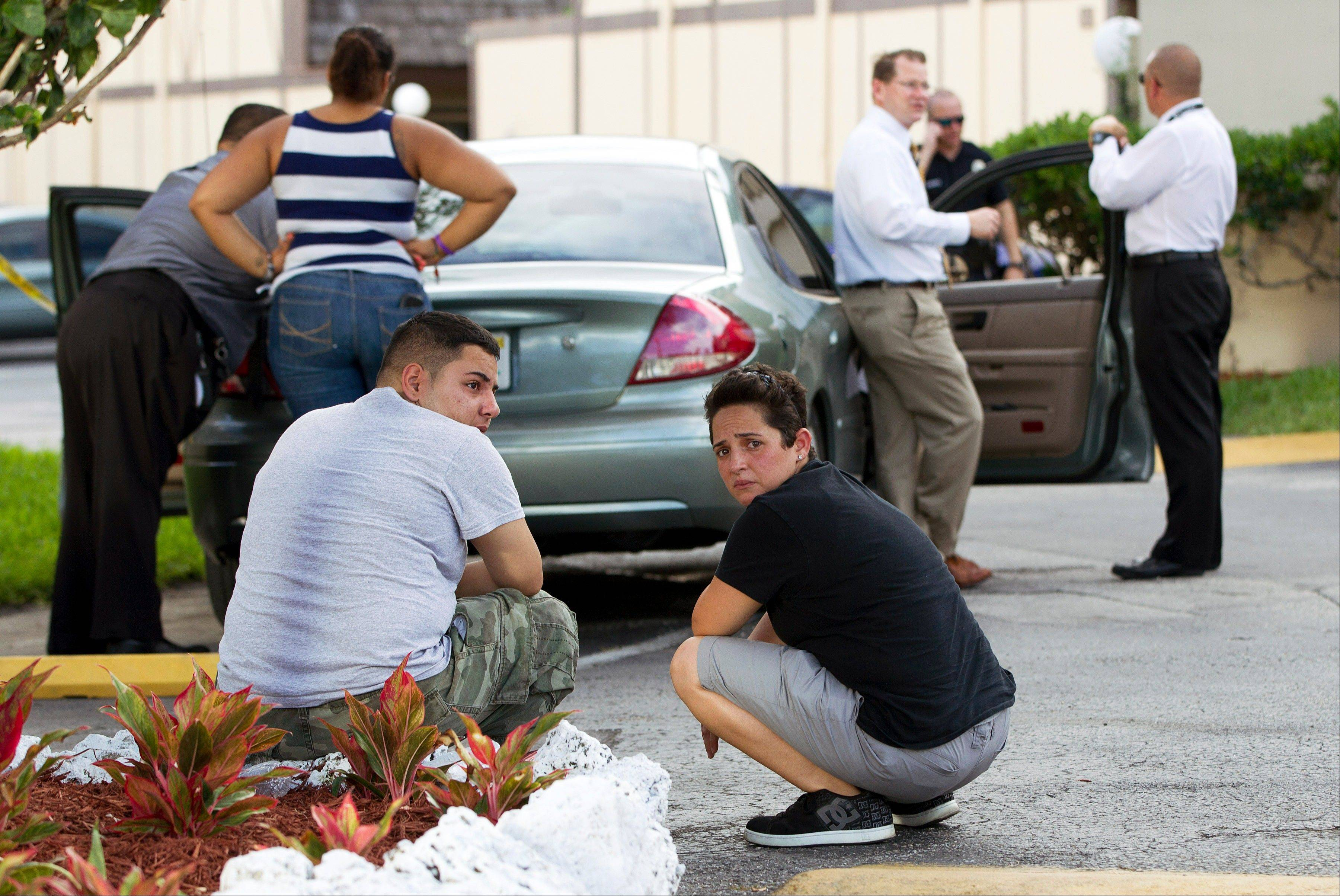 Two people sit behind a police car as Miami police officers investigate a murder on Thursday, Aug. 8, 2013 in Miami. Derek Medina, who authorities say fatally shot his wife ó and apparently then posted a photo of her body on Facebook ó turned himself in to police on Thursday.
