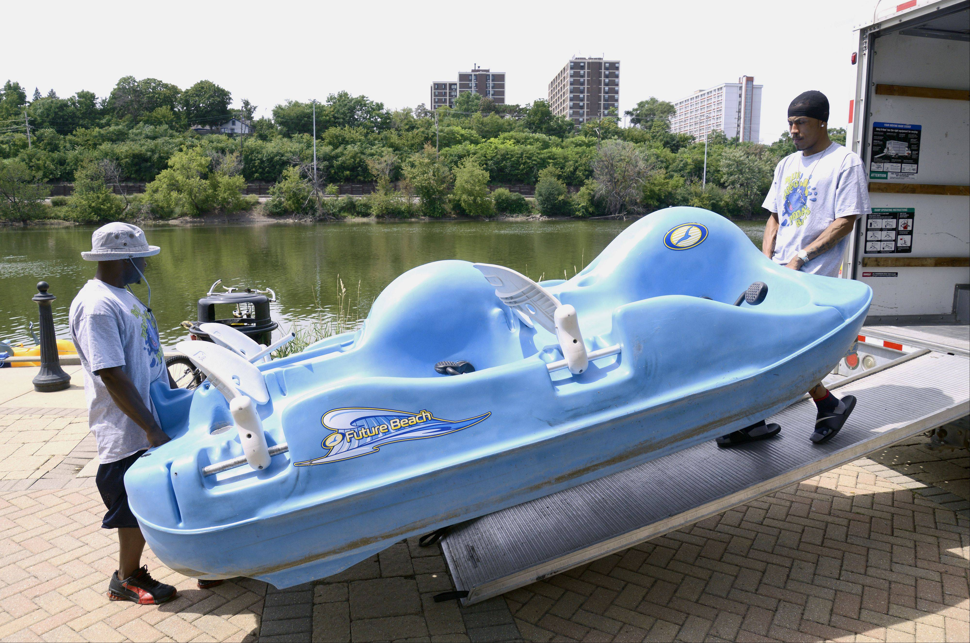 Justin Hodge, owner of Blue Hippo Pedal Boats, left, and employee Daniel Garcia, unload a four-seater as they set up for business Thursday at Festival Park in Elgin. Riders have a choice of a two-seater or a four-seater boat.