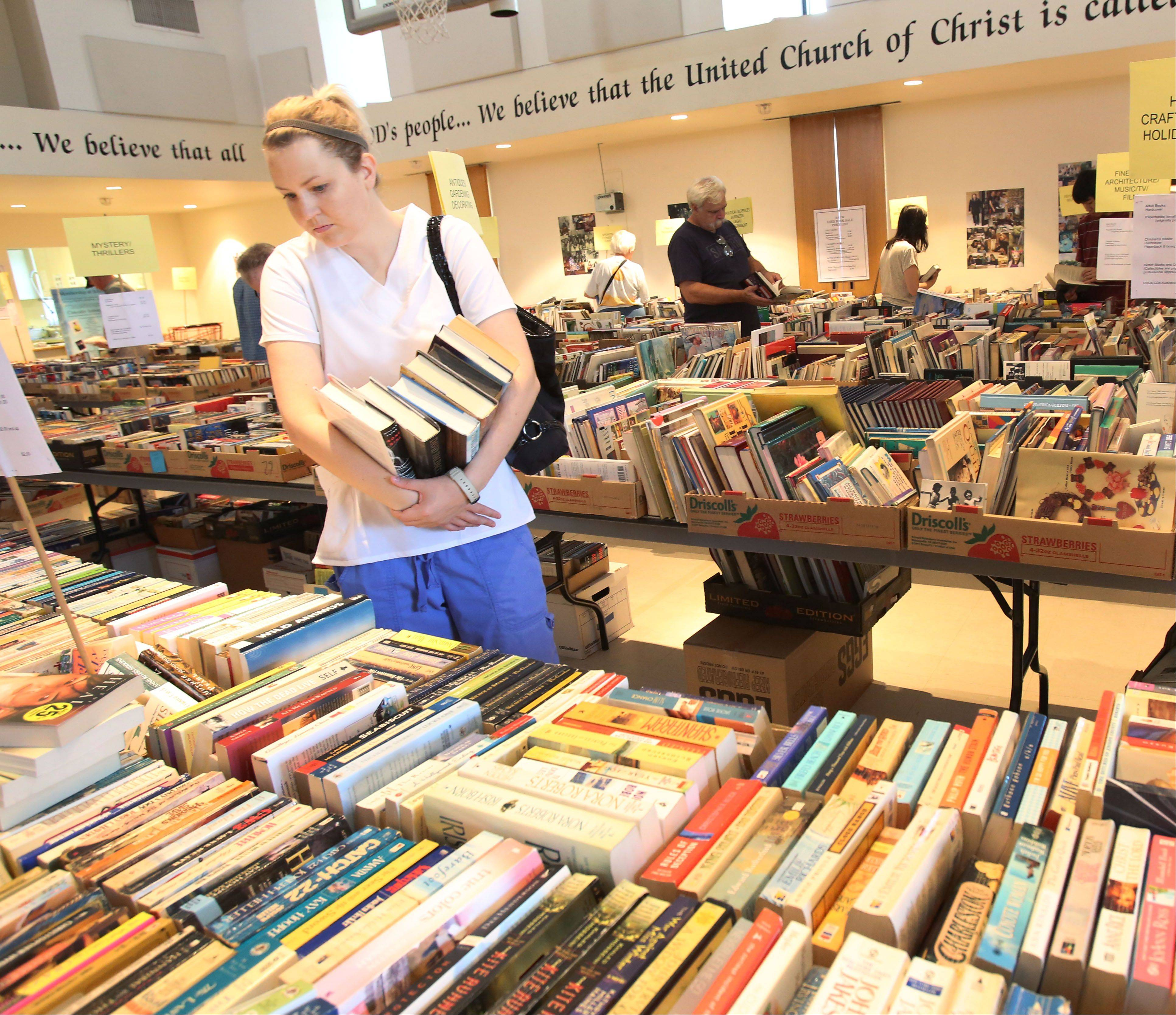 Desiree West of West Chicago checks out the selection Thursday at the annual used book sale sponsored by the Lombard Area AAUW at First Church of Lombard. Now in its 50th year, the sale continues through Saturday.