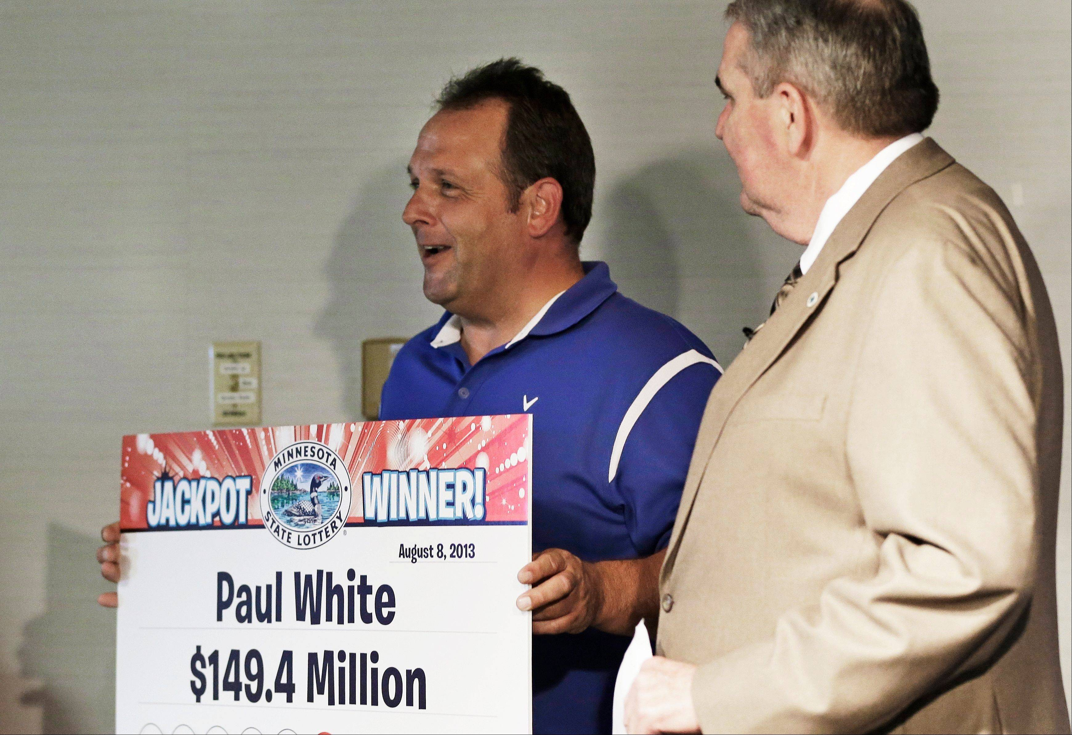 Paul White, of Ham Lake, Minn. holds up his winning amount as Minnesota Lottery executive director Ed Van Petten, right, looks on during news conference after White was announced as one of the winners of the $448.4 million Powerball Jackpot, Thursday, Aug. 8, 2013 in Minneapolis. White's share of the jackpot is $149.4 million. The woman at left is a co-worker friend.