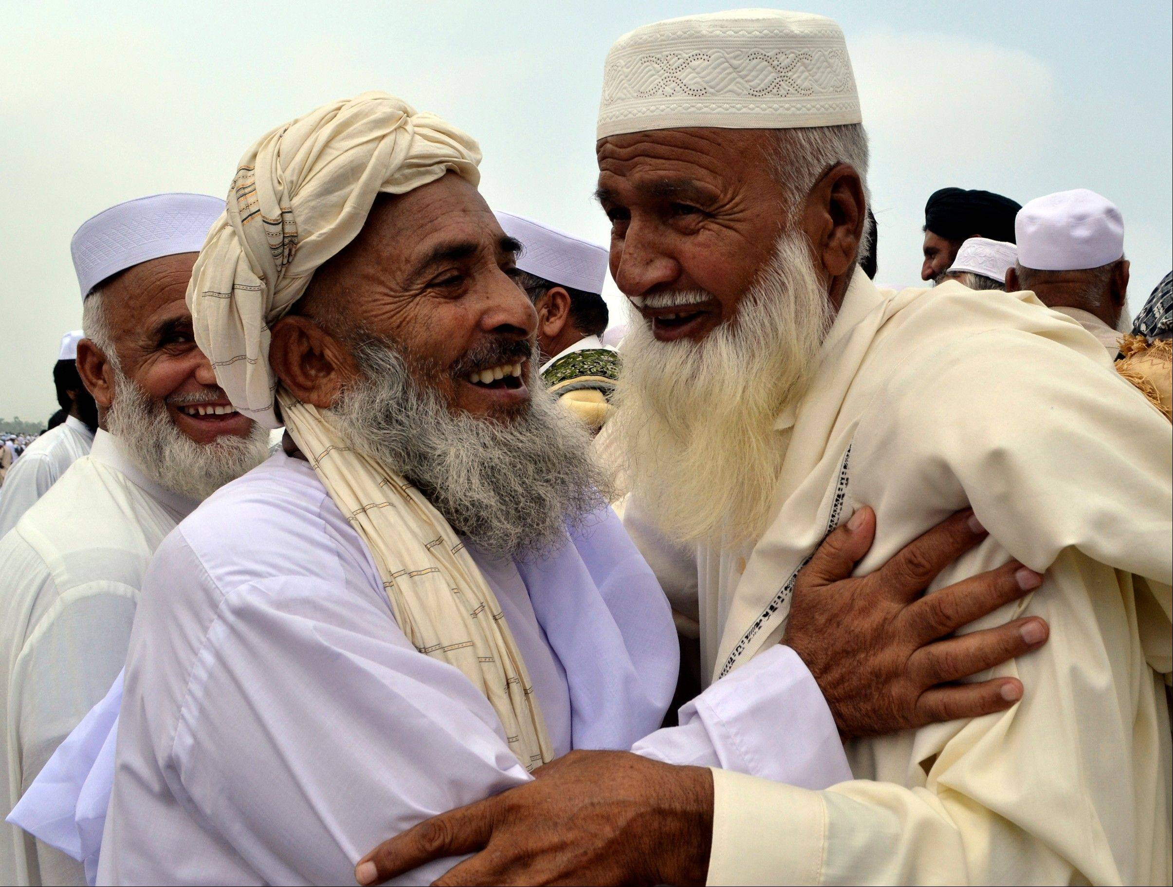 Afghan refugees living in Peshawar, Pakistan, greet each other during the Eid al-Fitr holiday that marks the end of the holy fasting month of Ramadan, Thursday, Aug. 8, 2013. Millions of Muslims began celebrating the end of Ramadan on Thursday with morning prayers.