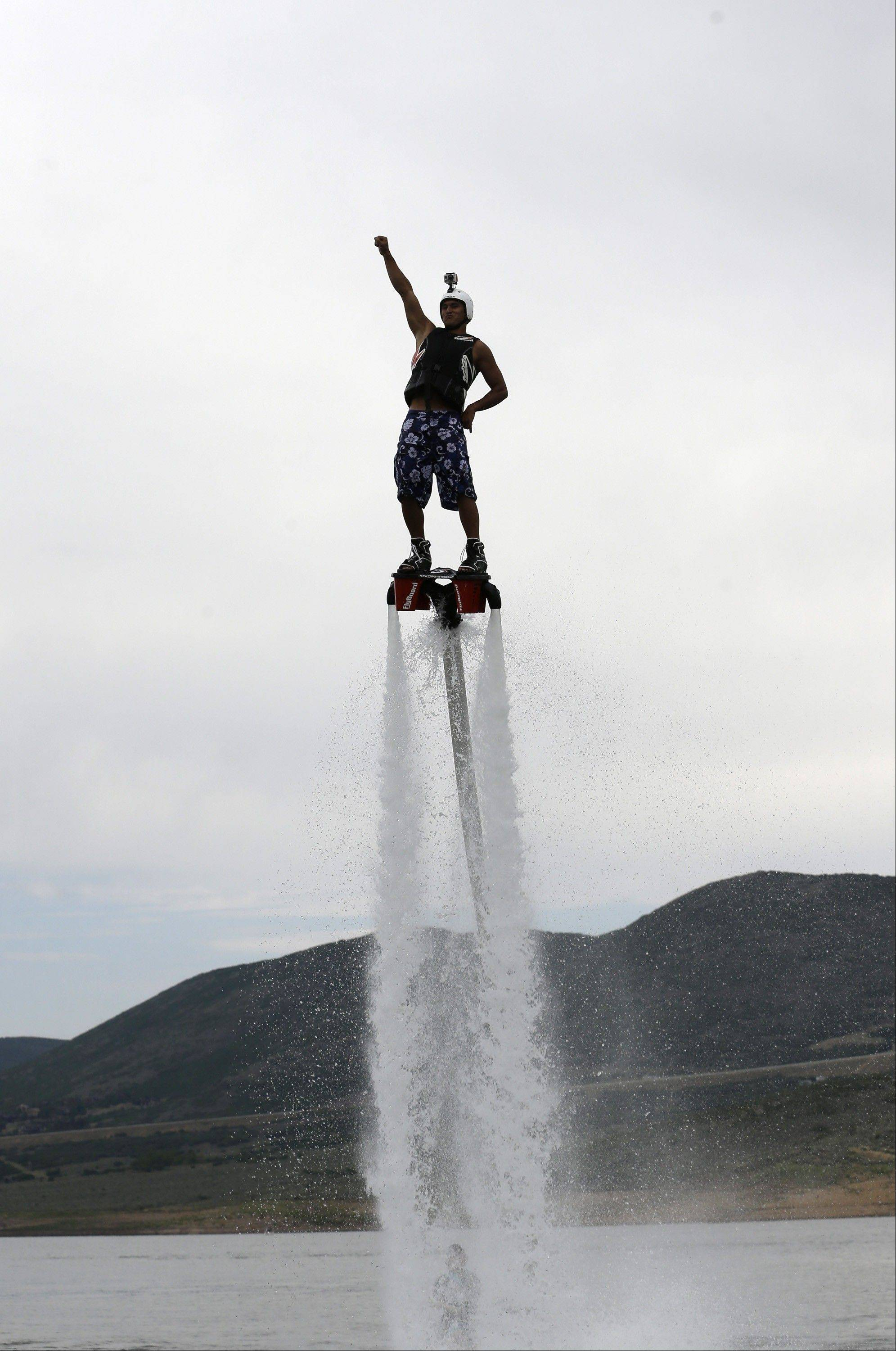 This July 24, 2013, photo, Rocky Mountain Flyboard instructor Jordan Wayment emerges from the water as he demonstrates the flyboard, on the Jordanelle Reservoir, at Jordanelle State Park, Utah. The Flyboard, which looks like a small snowboard attached to a hose, can propel you 45 feet in the air using water pumped from a personal watercraft like a Jet Ski to the base of the board.