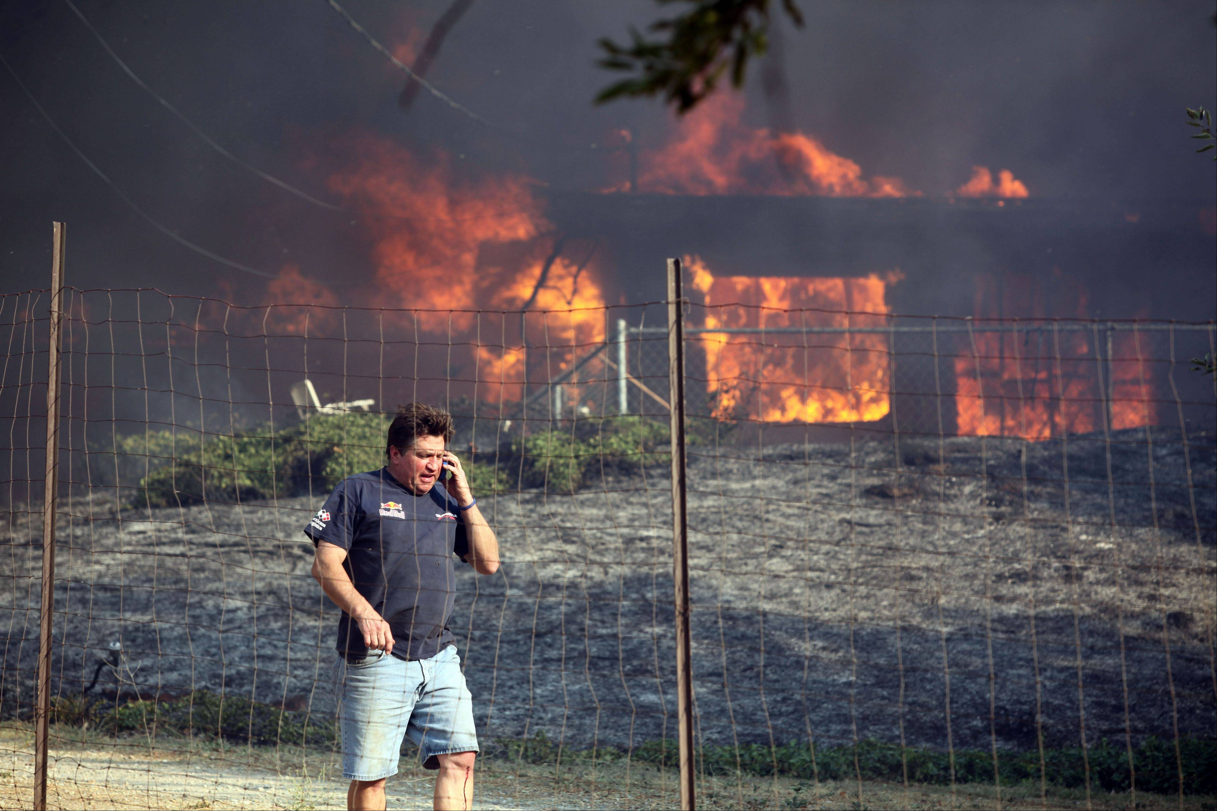 Dave Clark, of Twin Pines, tells a neighbor their house is ok as his own house burns on Wednesday, Aug. 7, 2013. Residents and sheriff's deputies were left without an escape route and stuck inside an evacuation area Wednesday night as a huge and growing Southern California wildfire left three people injured and burned homes.