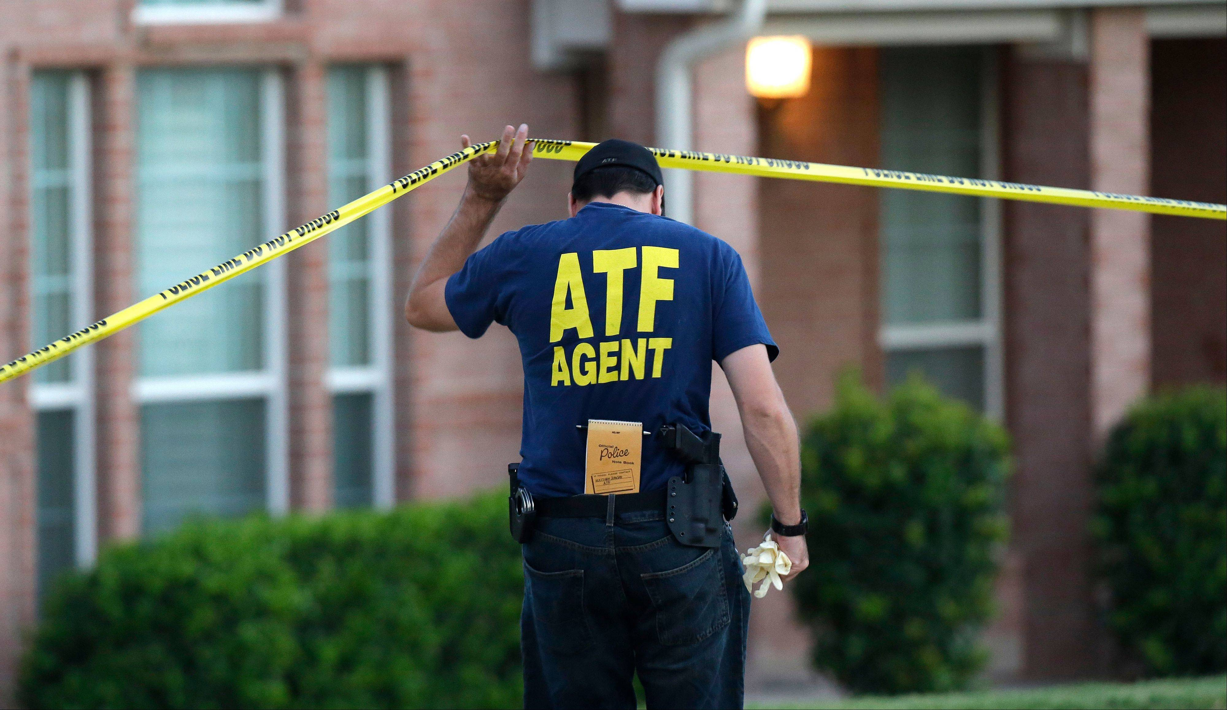 An ATF agent lifts crime scene tape outside the scene of two murders Thursday morning, Aug. 8, 2013, in DeSoto, Texas. Four people were killed at two different locations in South Dallas County and the suspected shooter is in police custody.