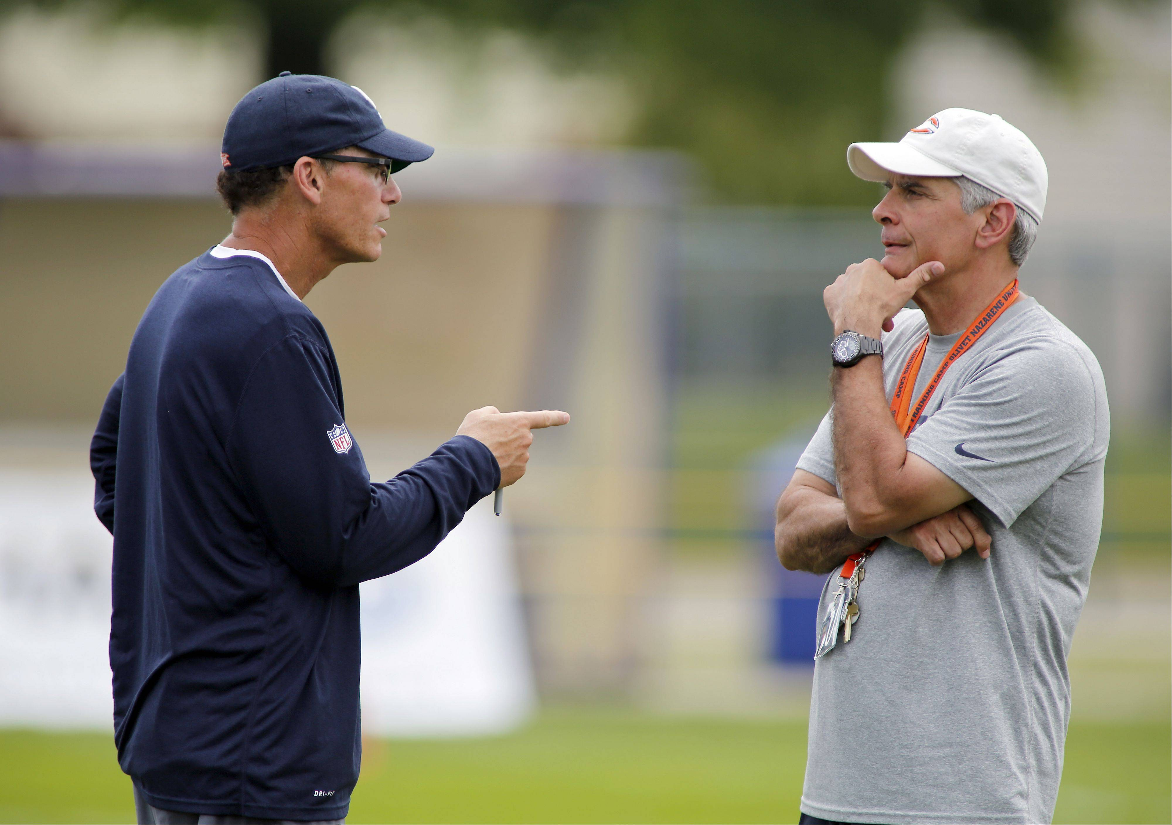 Bears coach Marc Trestman talks to general manager Phill Emery during training camp on the campus of Olivet Nazarene University in Bourbonnais.