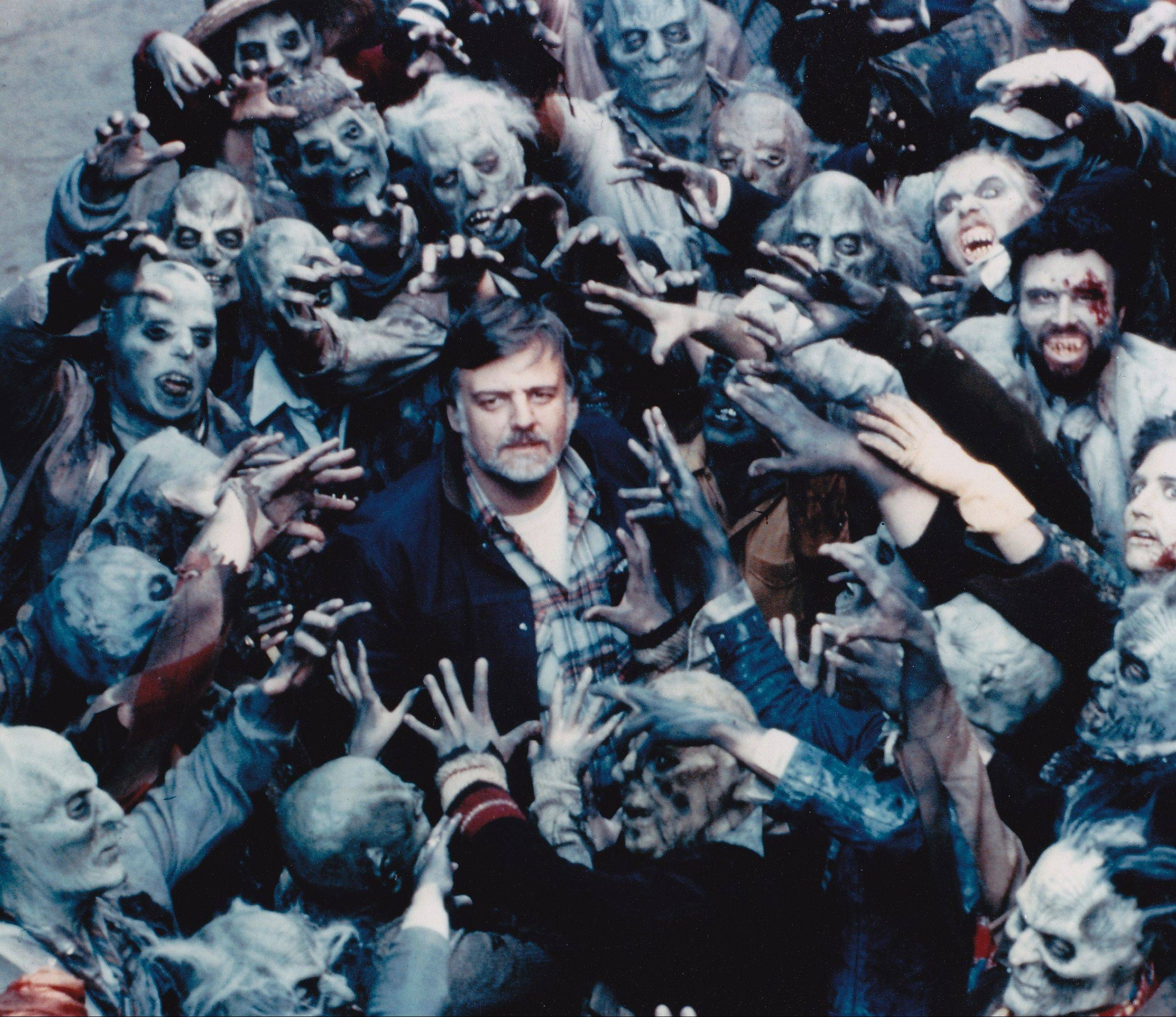 "Director George A. Romero (center), circa 1984, is mobbed by zombies on the set of ""Day of the Dead."" Romero will be at Flashback Weekend, Chicago's largest horror convention, today, Saturday and Sunday."