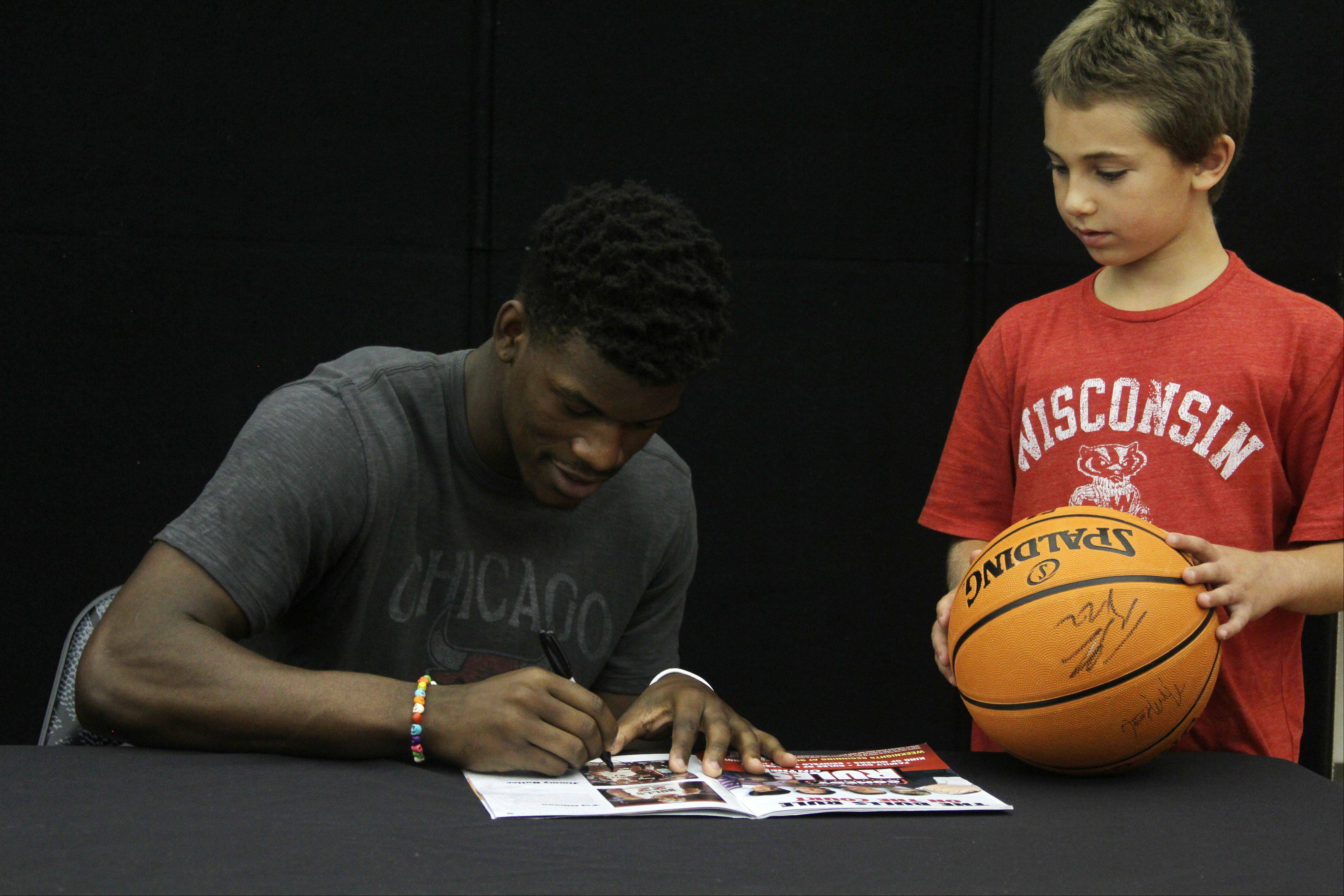 Jimmy Butler of the Chicago Bulls signs a book for camper Simon Schwartz, 8, Friday during an appearance at the Bulls/Sox Academy in Lisle. Butler spent more than an hour giving kids high-fives, posing for photos and signing memorabilia.