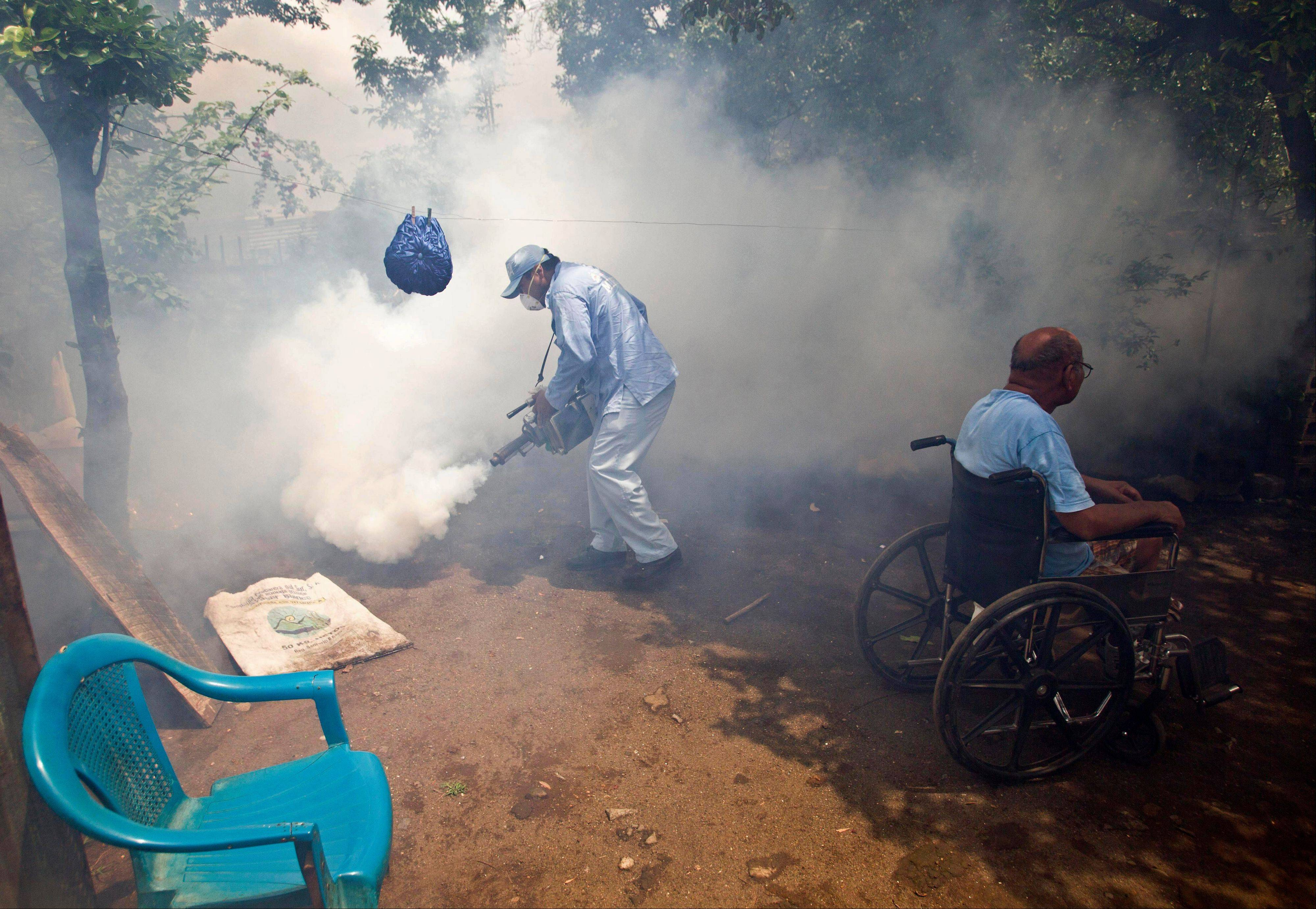 Associated Press/July 12, 2013 A worker from the health ministry fumigates the backyard of a home where the man who lives there sits in his wheelchair in the neighborhood of Waspam in Managua, Nicaragua.