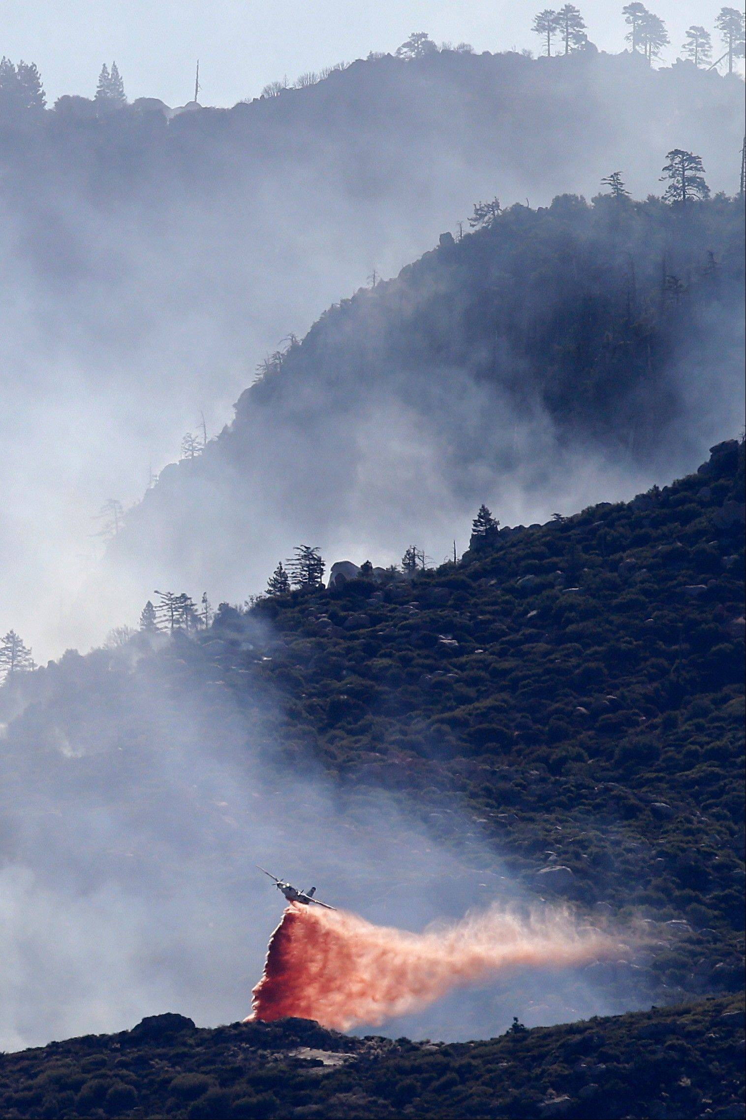 An air tanker drops fire retardant on a hot spot Friday as firefighters continue to battle a wildfire near Banning, Calif.