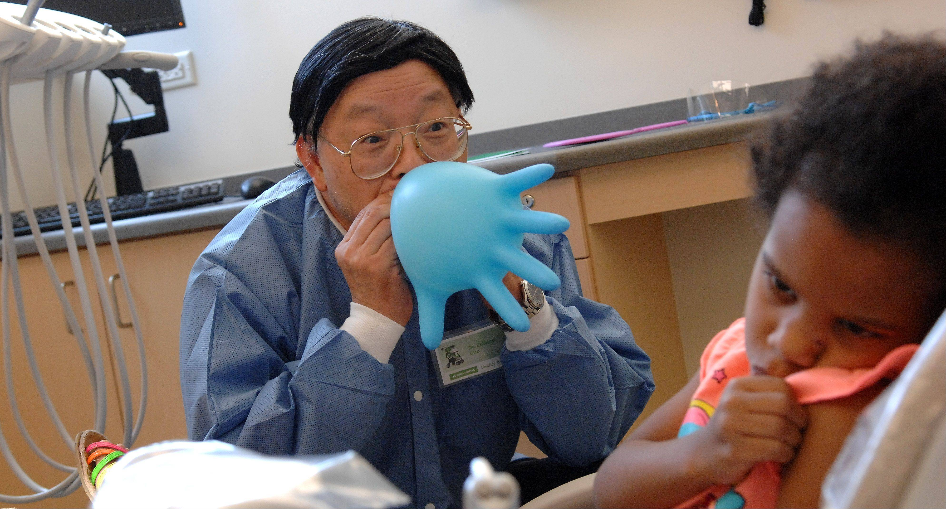 Dr. Edward Cho tries to get a nervous Nayomi Baumeister, 4, of Elgin to open up to him a little bit by making a balloon glove Friday as volunteers from the Delta Dental of Illinois Foundation provided free dental care to kids at Elgin Community College.