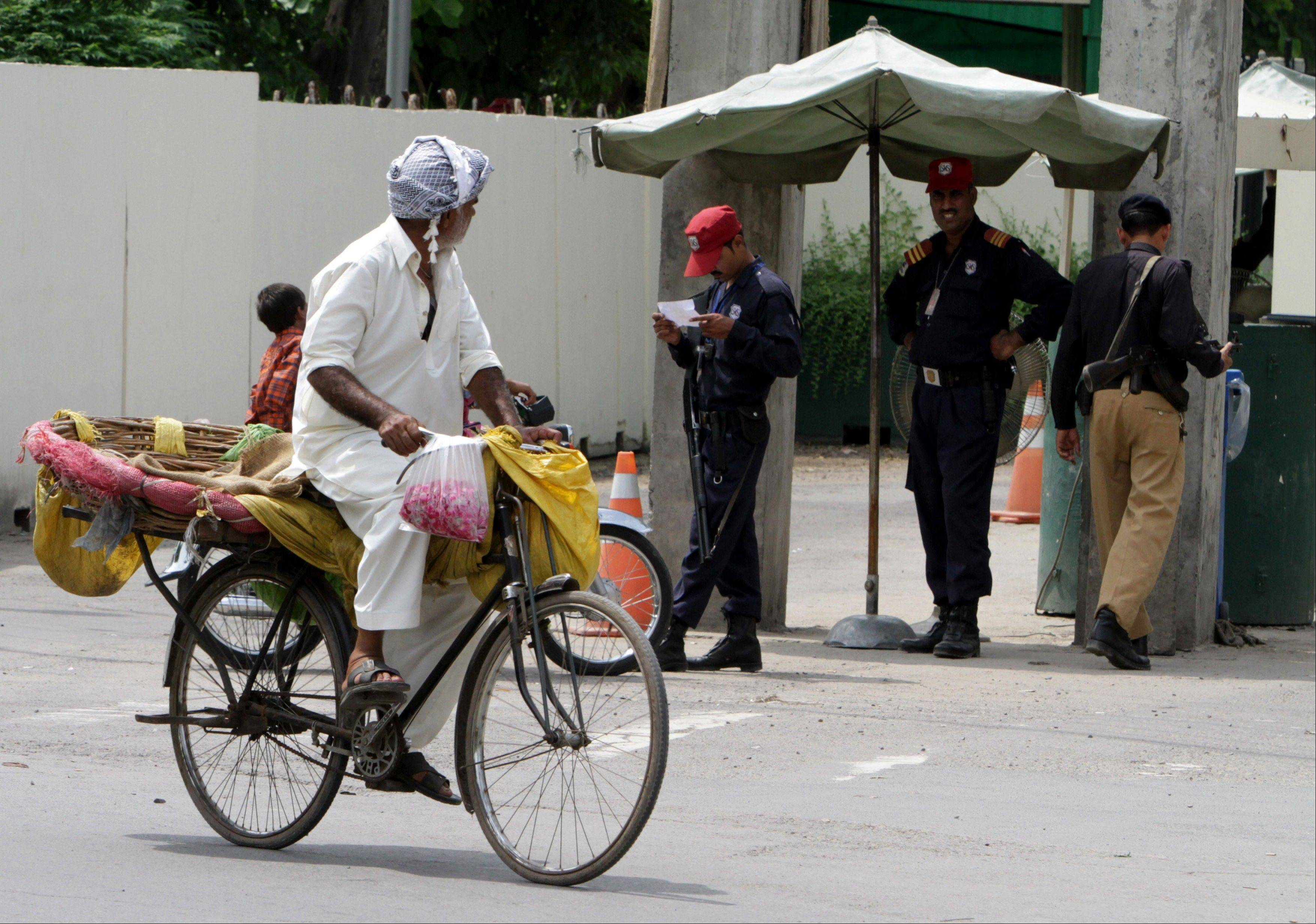 A Pakistani vendor rides his bicycle past the U.S. Consulate in Lahore, Pakistan, Friday, Aug. 9, 2013. The State Department warned Americans not to travel to Pakistan and evacuated nonessential government personnel from the country's second largest city of Lahore because of a specific threat to the consulate there, a U.S. official said Friday.