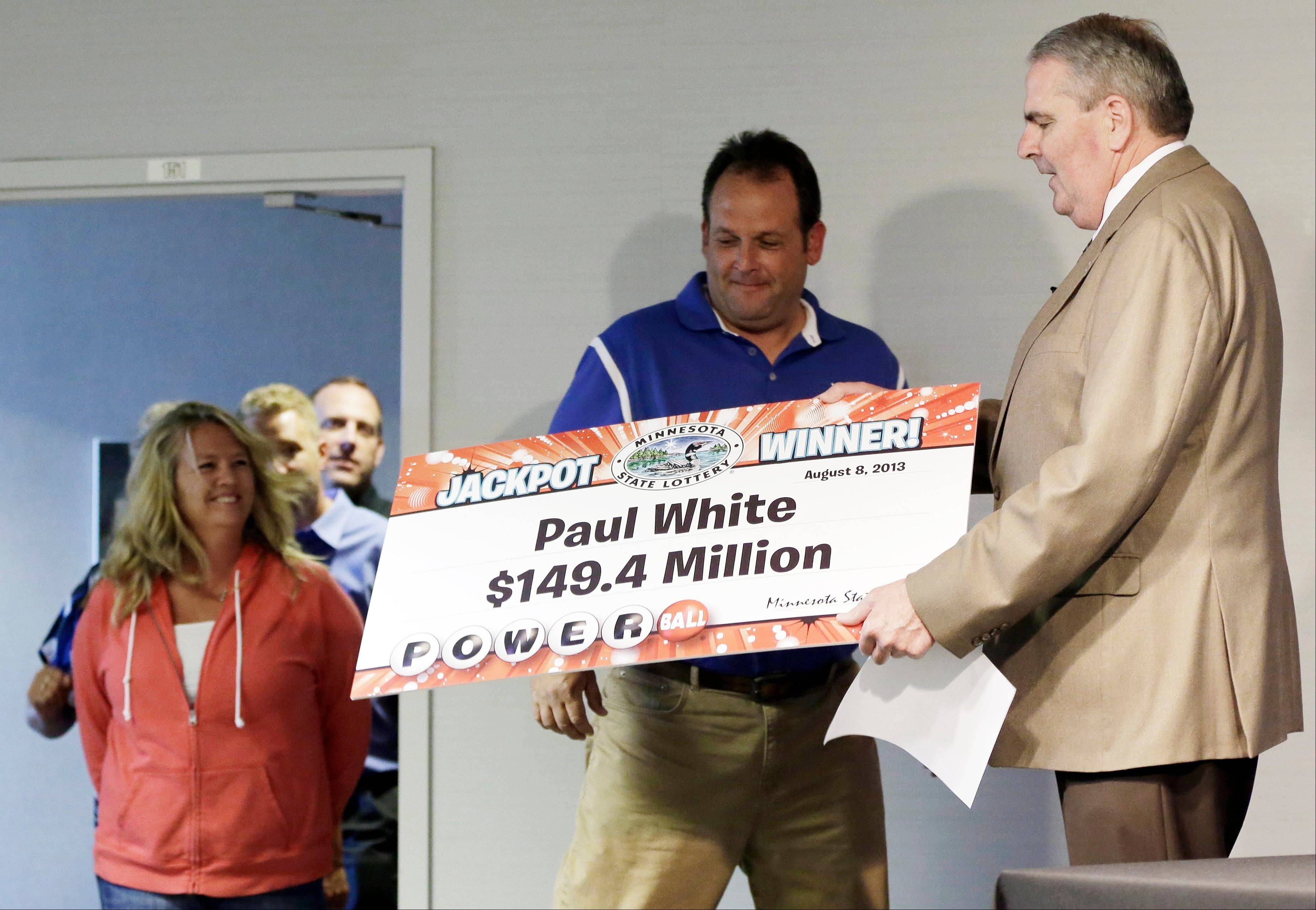 Paul White, of Ham Lake, Minn., is one of the winners of the $448.4 million Powerball Jackpot, Thursday, Aug. 8, 2013 in Minneapolis. White's share of the jackpot is $149.4 million. At rear left is White's girlfriend, Kim VanReese.