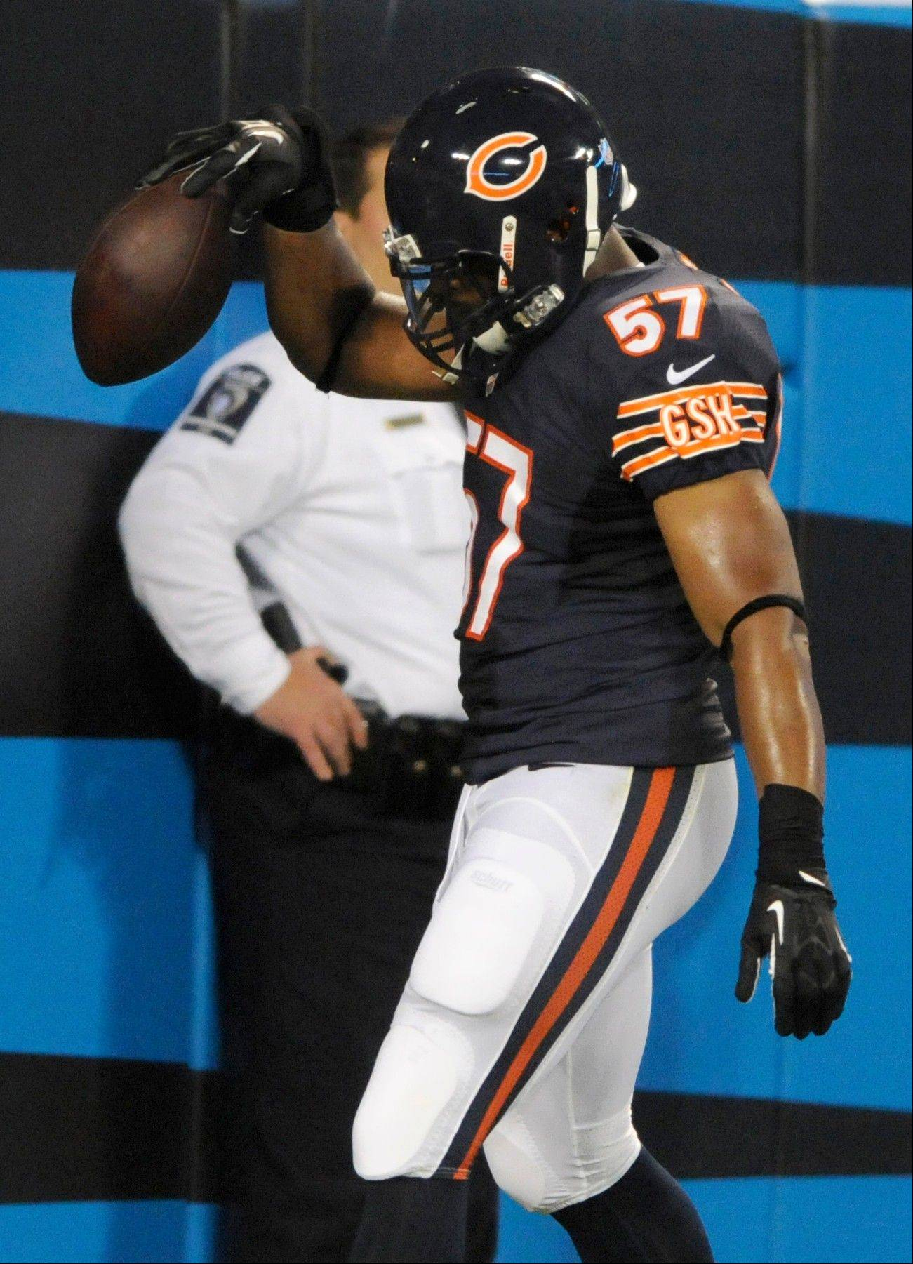 Chicago Bears' Jon Bostic (57) spikes the ball in the end zone after returning an interception for a touchdown against the Carolina Panthers during the first half of a preseason NFL football game in Charlotte, N.C., Friday, Aug. 9, 2013. (AP Photo/Mike McCarn)