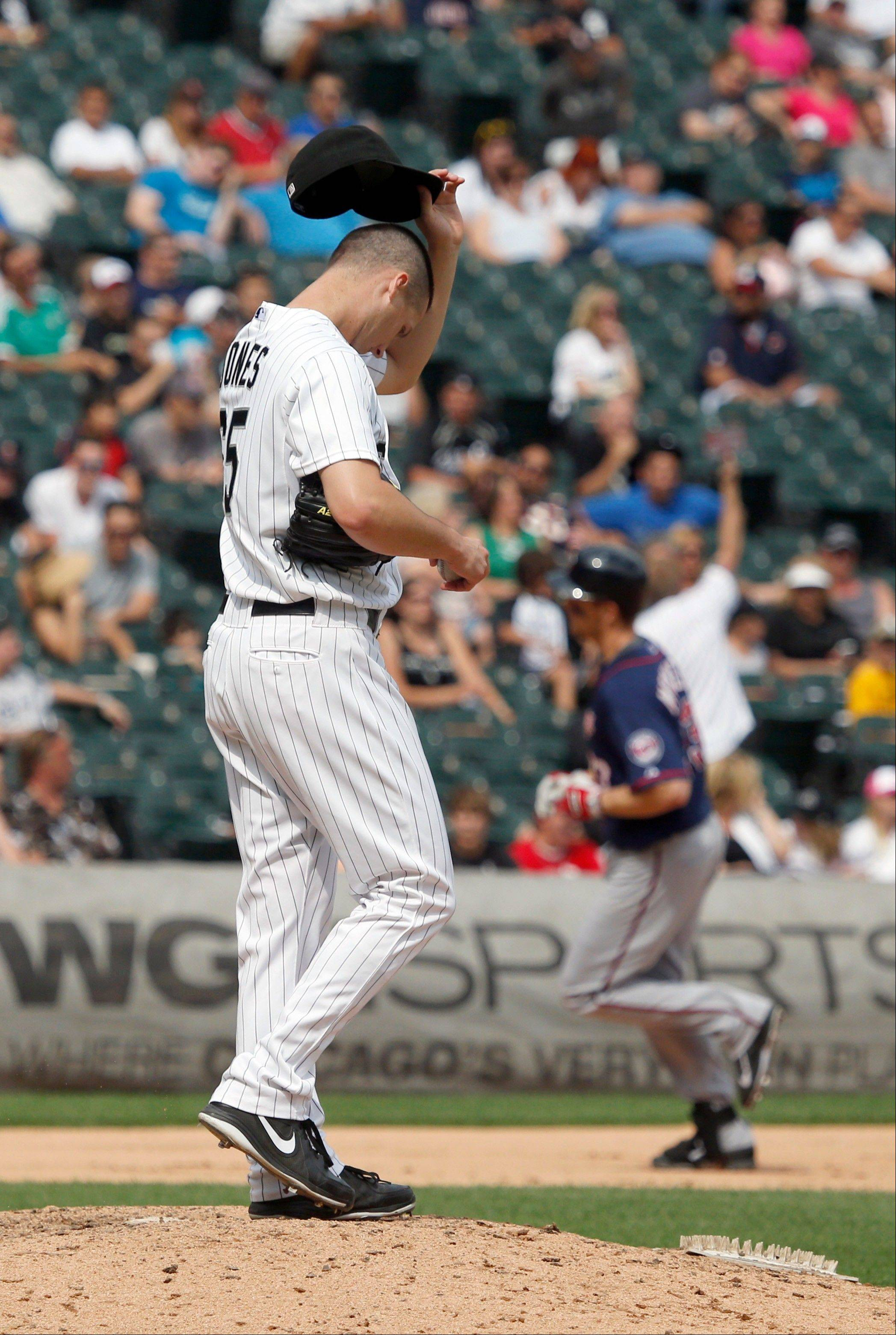 Chicago White Sox relief pitcher Nate Jones, left, wipes his face after giving up a grand slam to Minnesota Twins' Justin Morneau, rear right, during the seventh inning of a baseball game Friday, Aug. 9, 2013, in Chicago. Joe Mauer, Clete Thomas, and Pedro Florimon also scored on the play. (AP Photo/Charles Rex Arbogast)