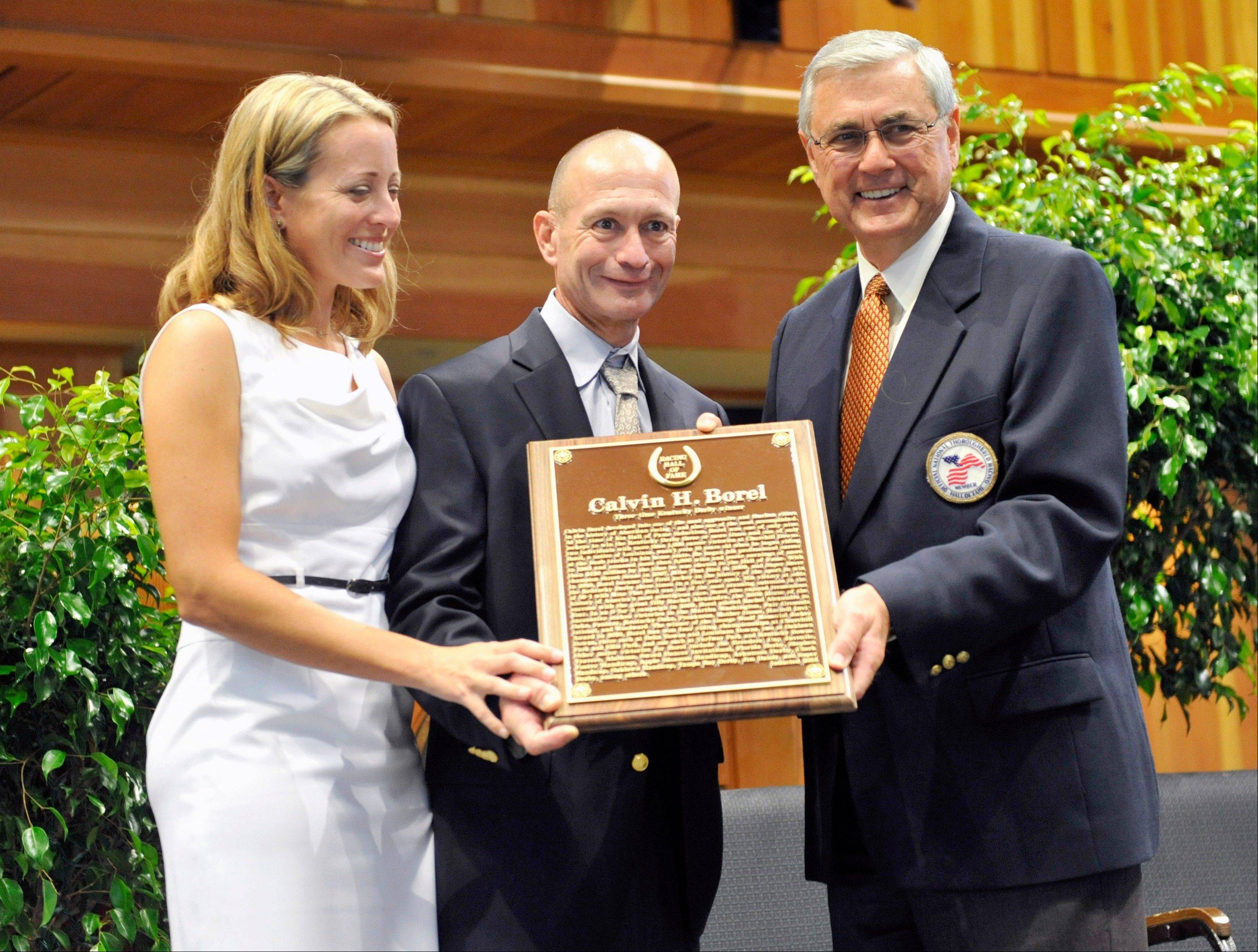 Lisa Borel ,left, stands with her husband Inductee Calvin Borel as he is presented with his plaque by fellow Hall of Fame trainer Carl Zafzger, right, during the National Museum of Racing's Hall of Fame induction ceremony at the Fasig-Tipton Humphrey S. Finney Pavilion in Saratoga Springs, N.Y., Friday Aug. 9, 2013. (AP Photo/Hans Pennink)