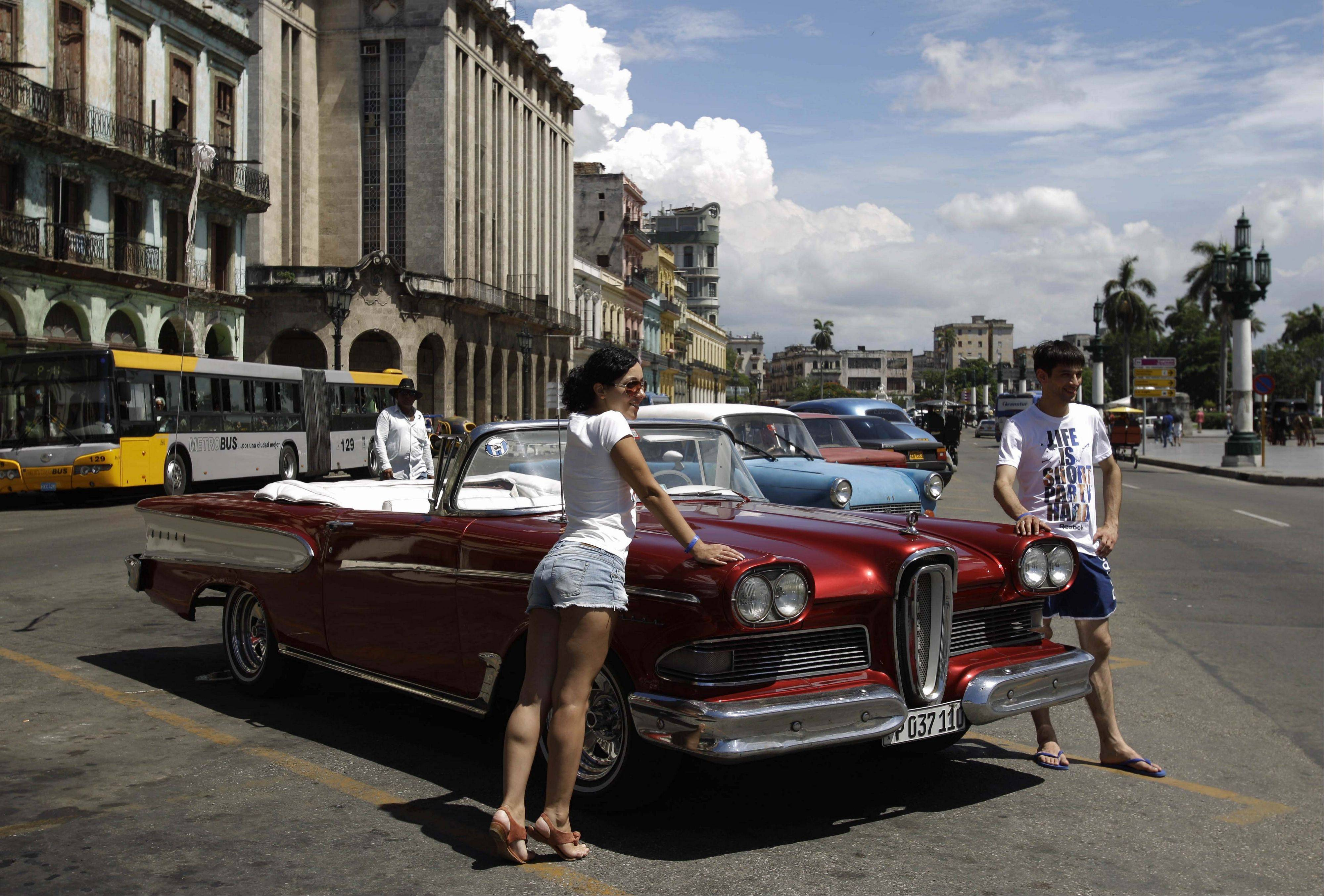 Tourists pose for a photo with a classic American car in Havana, Cuba.