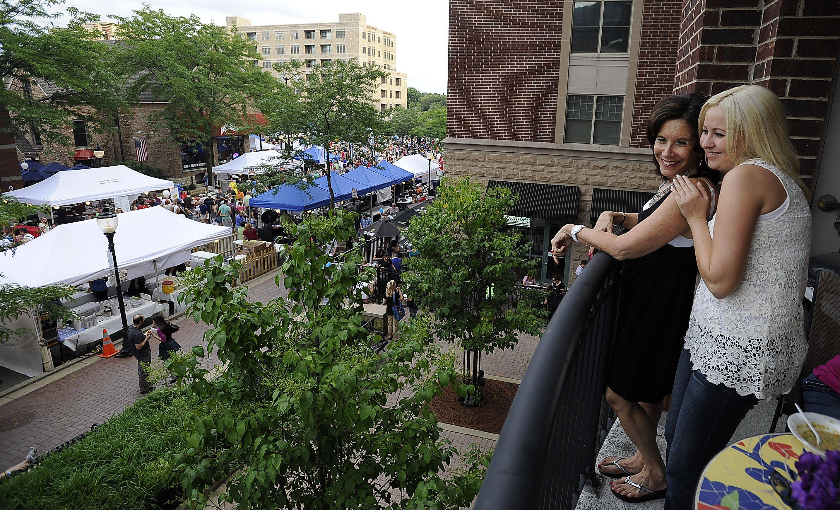 Mark Welsh/mwelsh@dailyherald.com Hundreds of people attend the Mane Event in downtown Arlington Heights on Friday including Tammy Green of Grayslake (front) and her friend Minda Smith of Vernon Hills who take in the sights from high above.