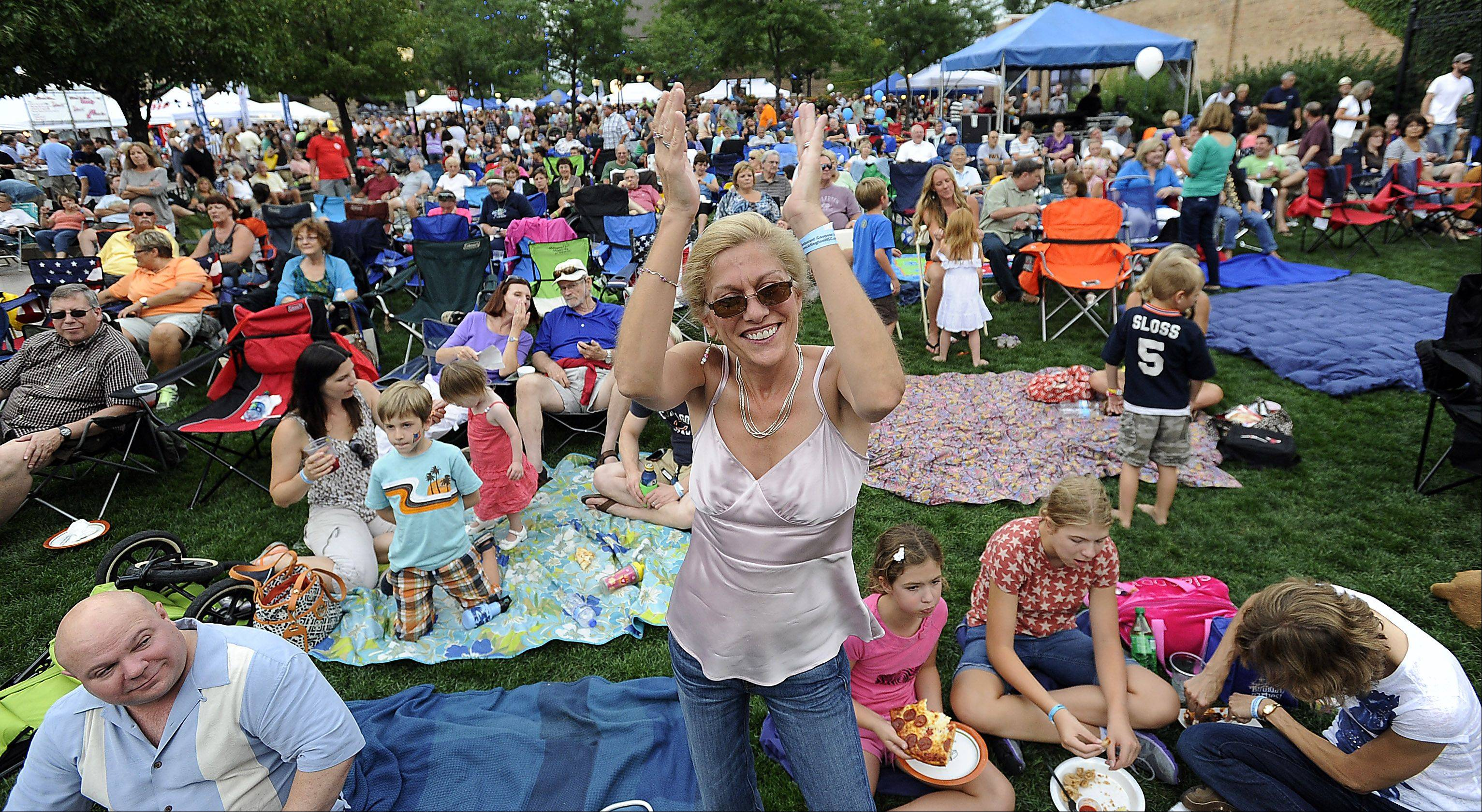 Mark Welsh/mwelsh@dailyherald.comDancing to the the song Blurred Lines played by the band on stage, Paula Euchner of Arlington Heights celebrates at the Mane Event in downtown Arlington Heights on Friday.