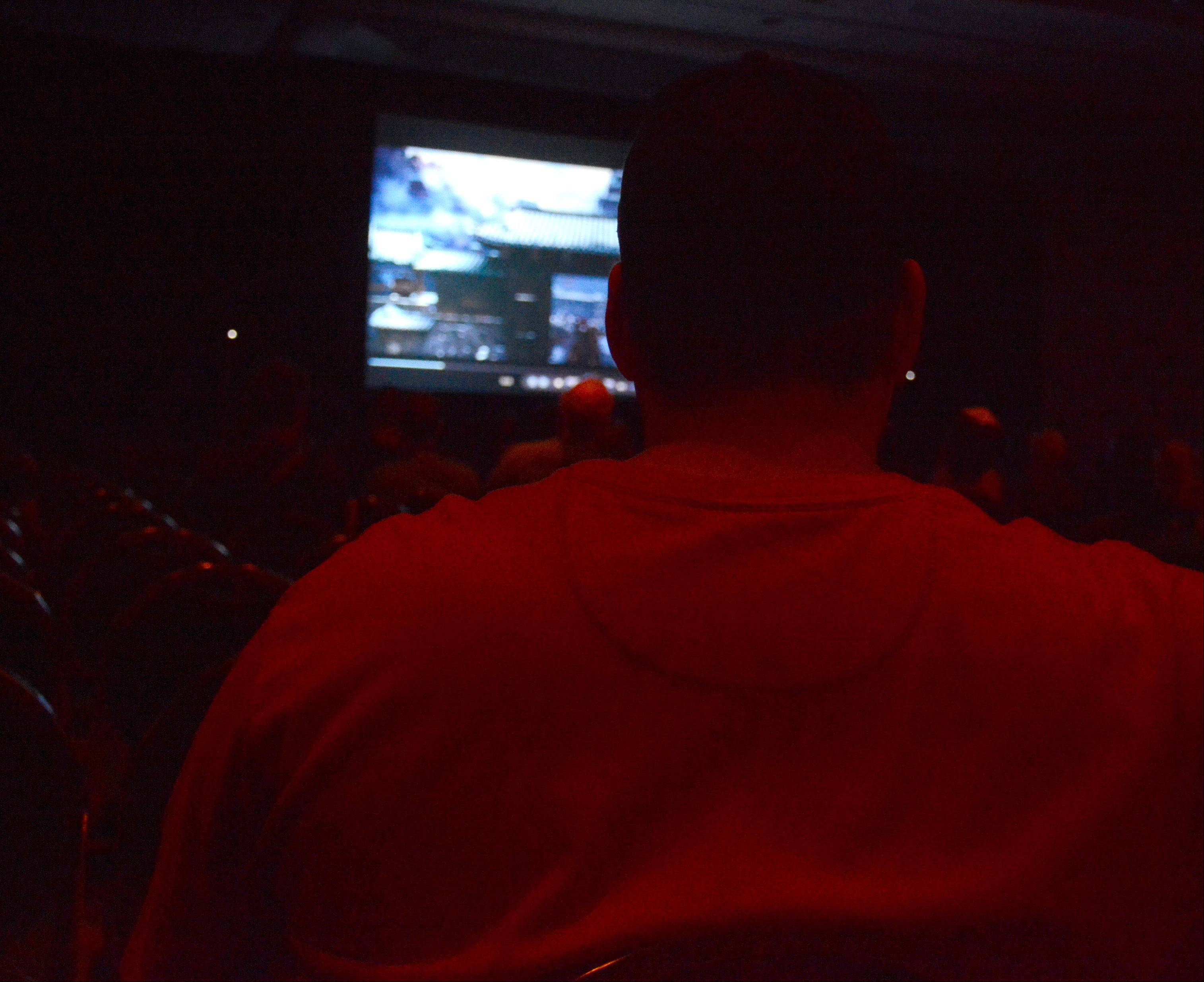 Lee Tapscott, of Indianapolis watches movie trailers during the trailer park production at Comic Con .