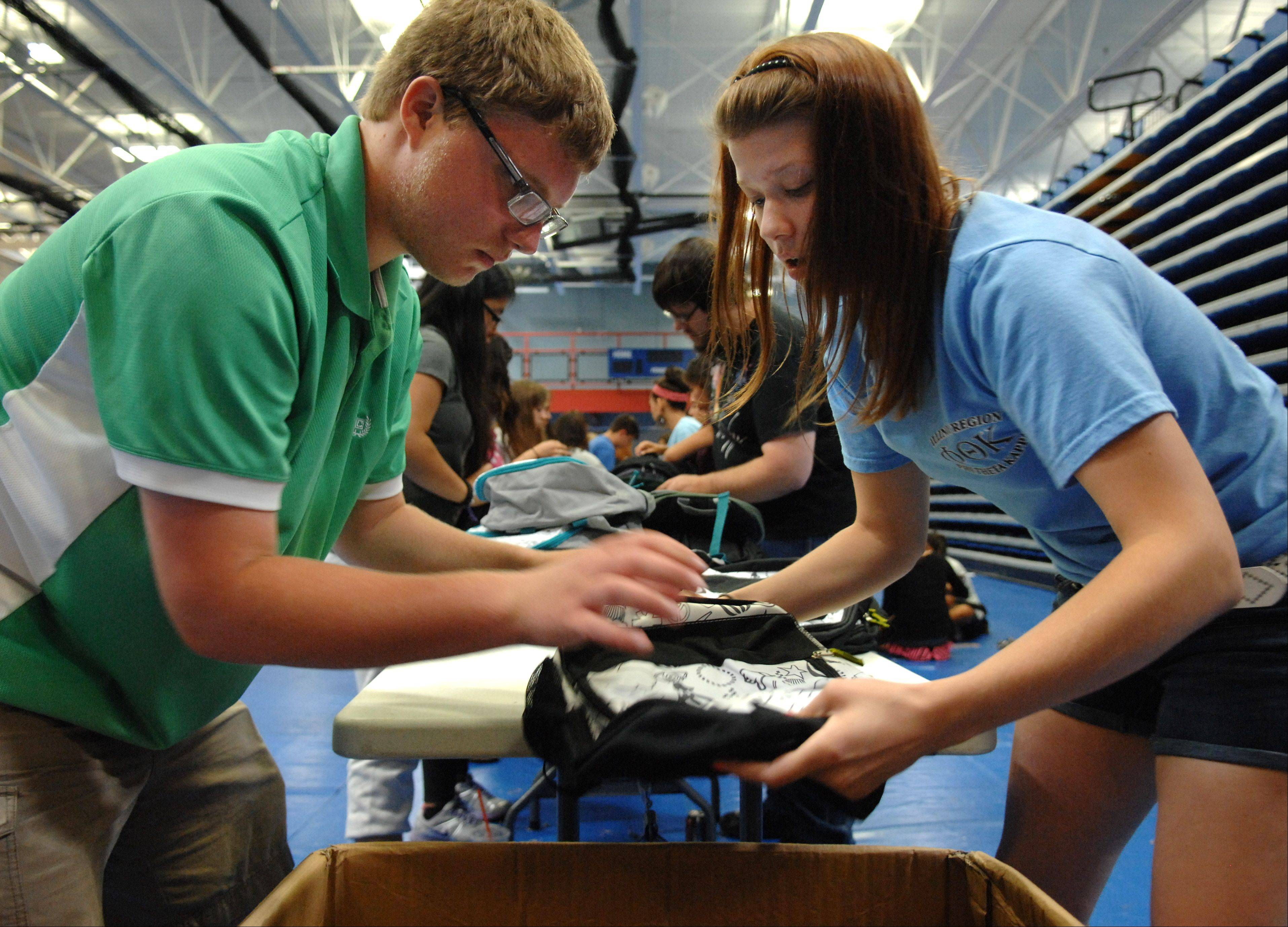 Volunteers Jacob Anderson of South Elgin and Libby Harvey of St. Charles pack donated school supplies into backpacks Friday for Elgin Community College's annual school supply giveaway. The packing started Thursday afternoon for the Saturday giveaway. They packed about 1,800 backpacks.