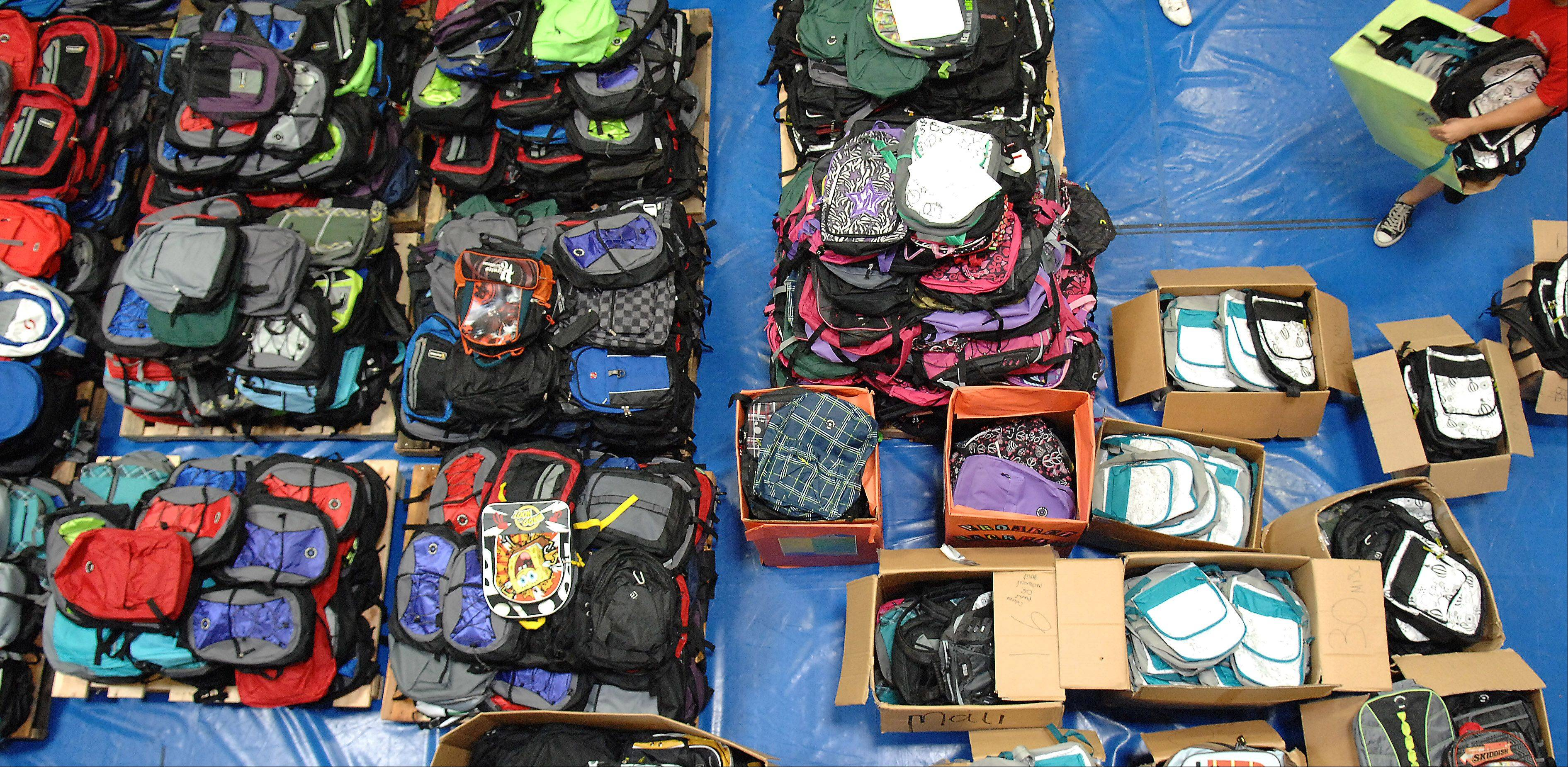 Volunteers packed about 1,800 backpacks with donated school supplies for Elgin Community College's annual school supply giveaway Saturday morning.
