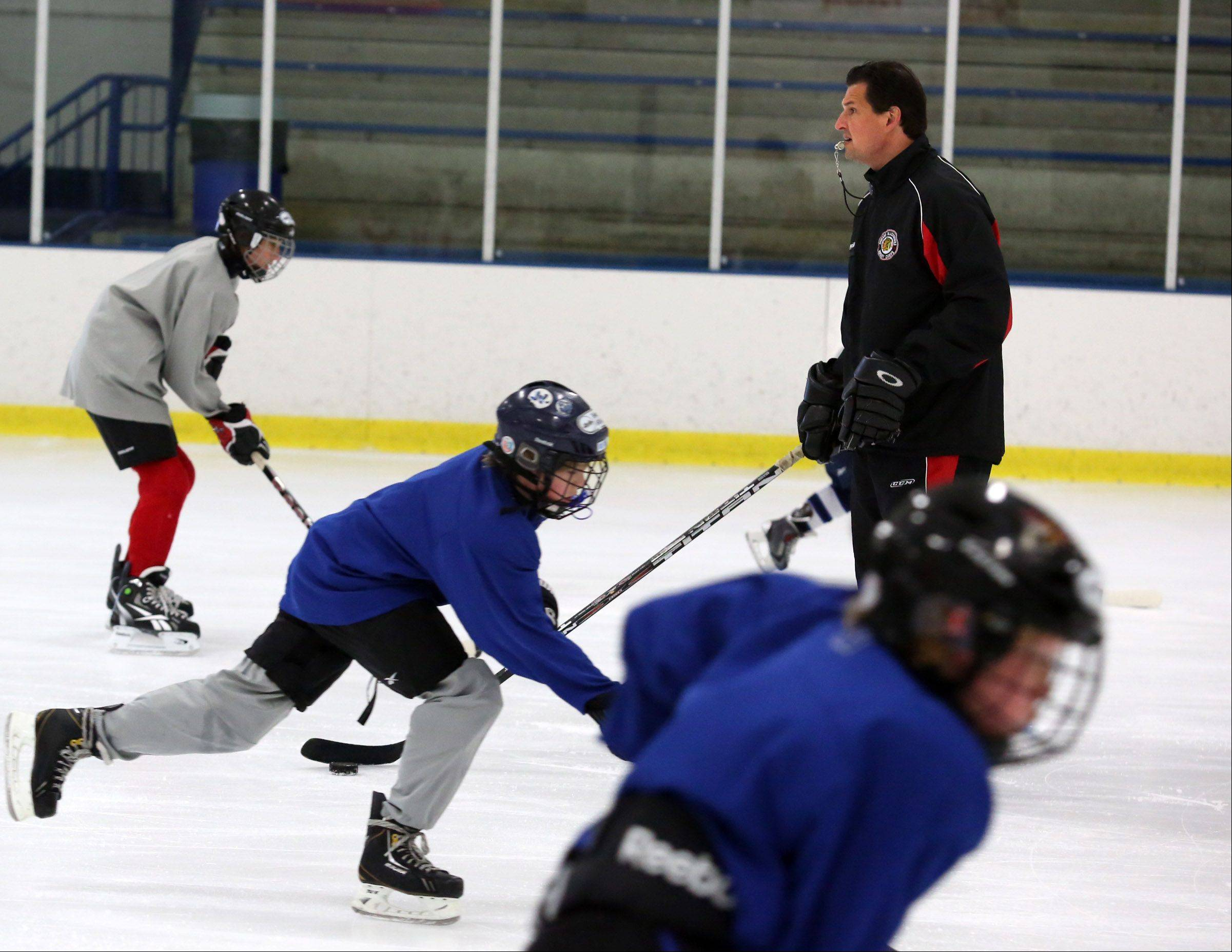 Eddie Olczyk, television color analyst for the Chicago Blackhawks, runs drills during a hockey camp at Glacier Ice Arena in Vernon Hills on Friday.