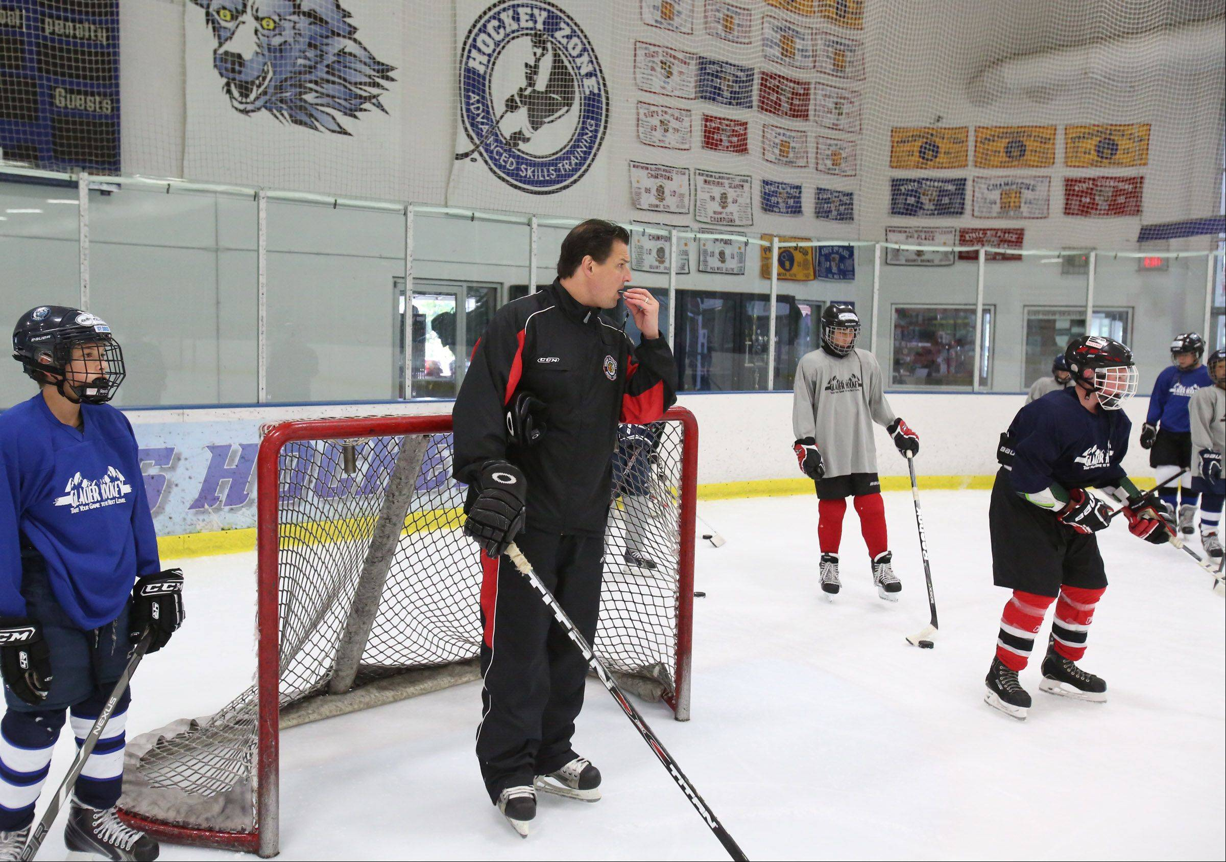 Eddie Olczyk, current television color analyst and former player for the Chicago Blackhawks, provides instruction during a hockey camp Friday at Glacier Ice Arena in Vernon Hills.
