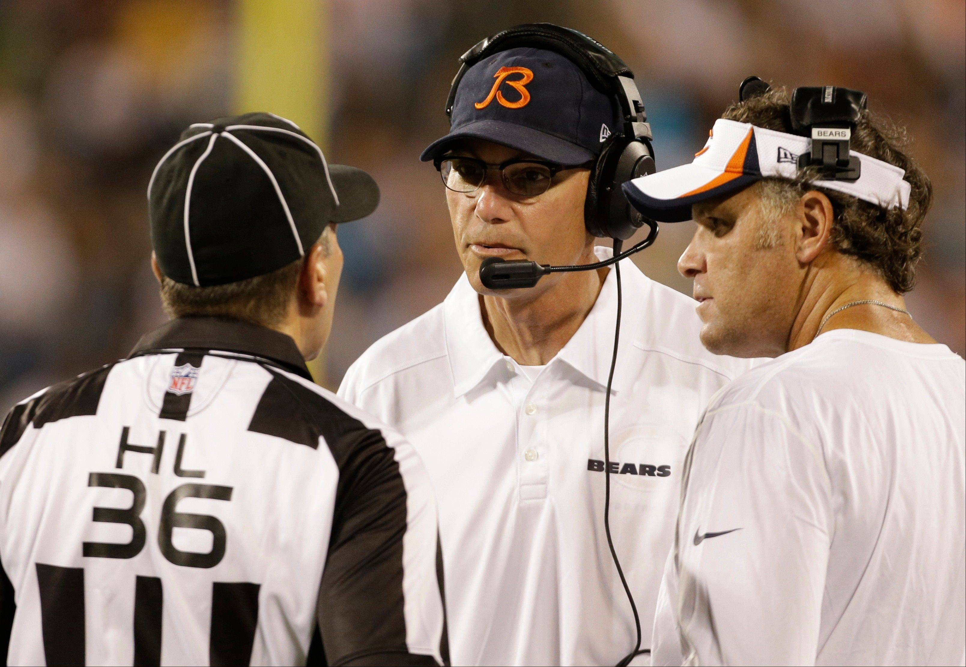 Chicago Bears head coach Marc Trestman, center, argues a call with head linesman Tony Veteri, left, during the first half of a preseason NFL football game in Charlotte, N.C., Friday, Aug. 9, 2013.