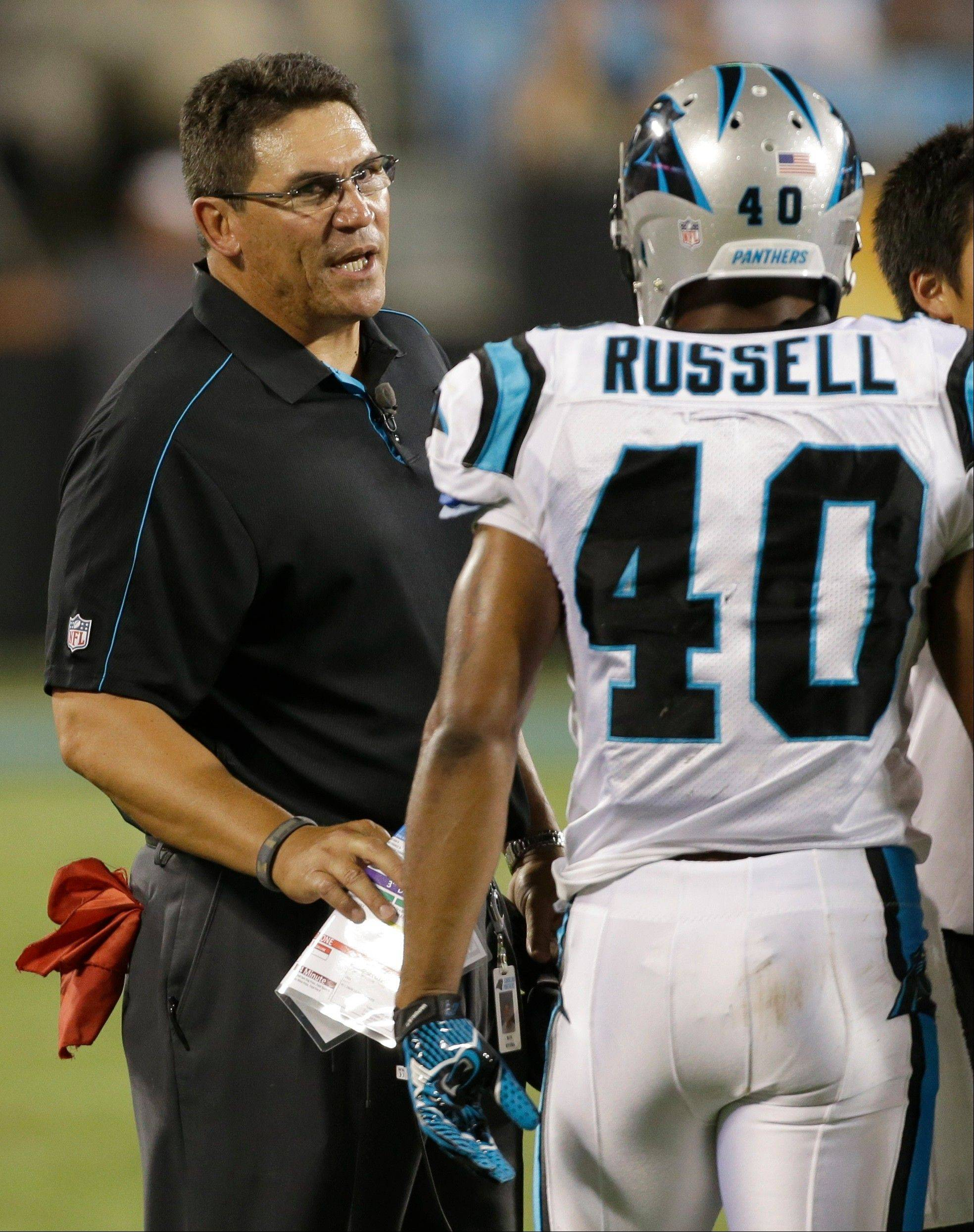 Carolina Panthers coach Ron Rivera, left, talks with Anderson Russell during the second half of a preseason NFL football game against the Chicago Bears in Charlotte, N.C., Friday, Aug. 9, 2013.