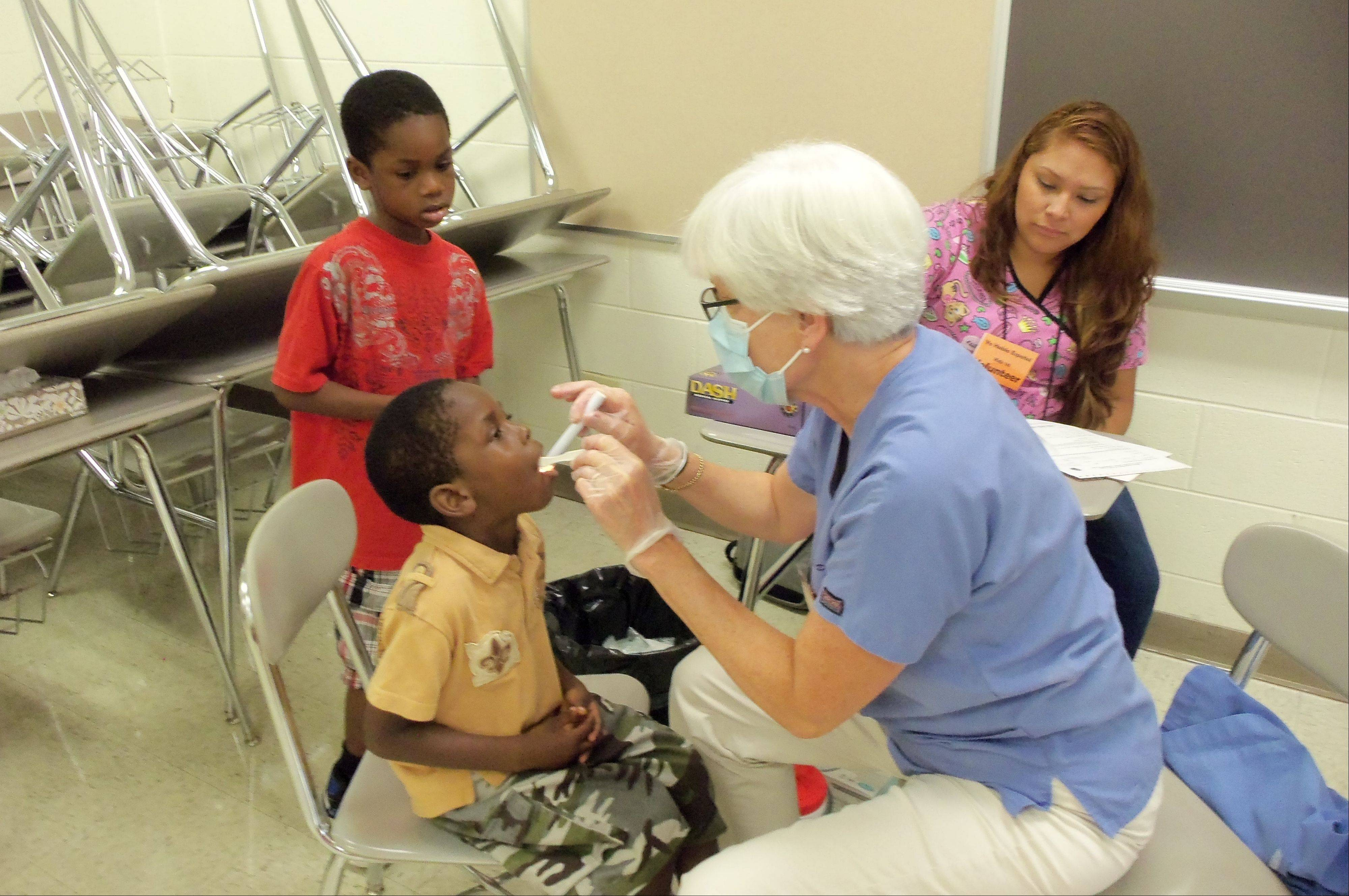 Quinton Payne, 7, of Waukegan watches as his brother, Quintarion Payne, 4, of Waukegan has his teeth examined by Dr. Christina O'Connor, a volunteer dentist at the Kids 1st Health Fair.