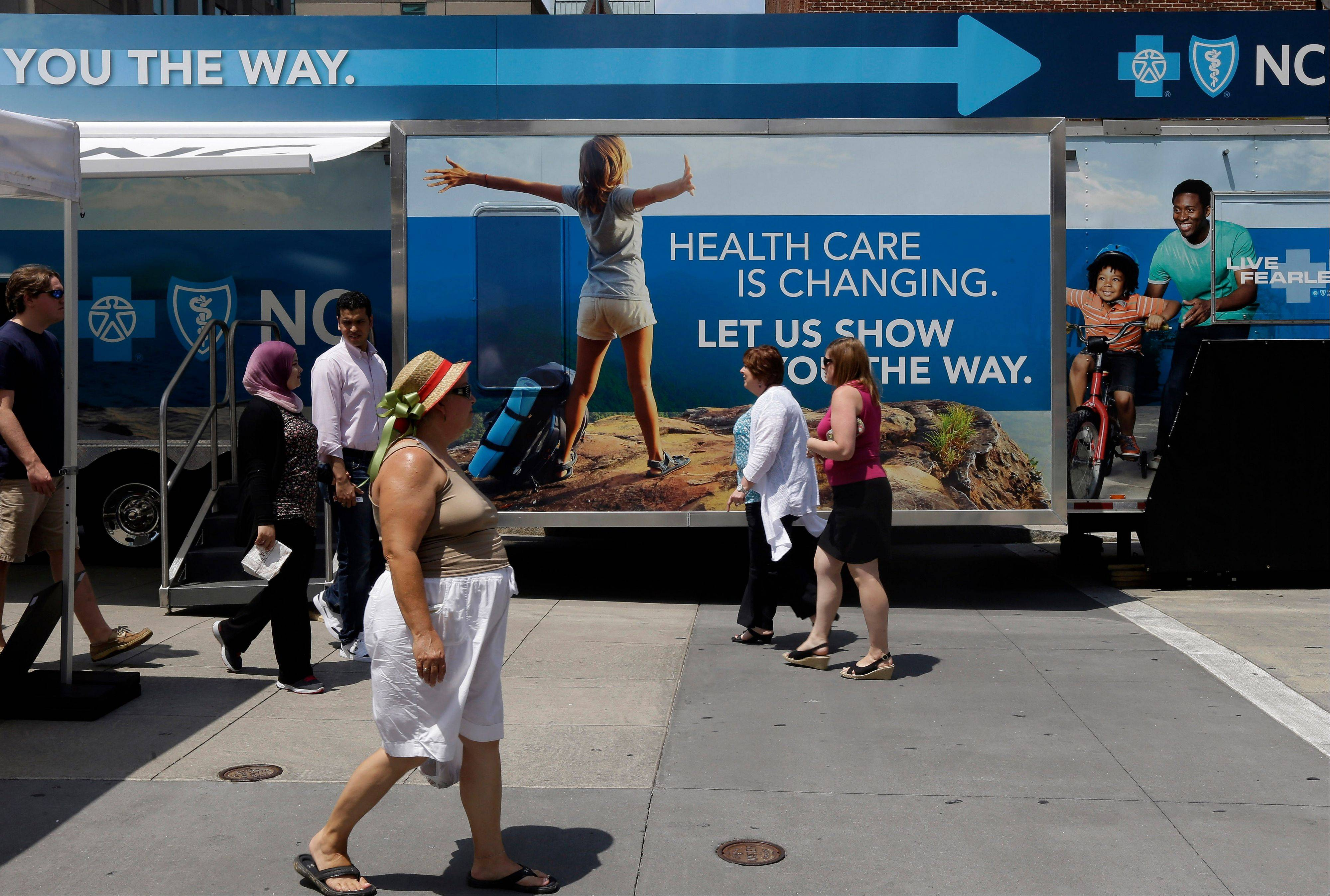 Pedestrians pass by a Blue Cross Blue Shield of North Carolina trailer at the downtown farmer's market in Raleigh, N.C.