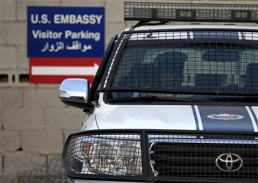 A Bahraini police officer sits in a police car at a new checkpoint near the U.S. Embassy in Manama, Bahrain. Eighteen of the 19 U.S. embassies and consulates that were closed in the Middle East and Africa because of a terrorist threat will reopen on Sunday or Monday, the State Department said Friday, Aug. 9, 2013.