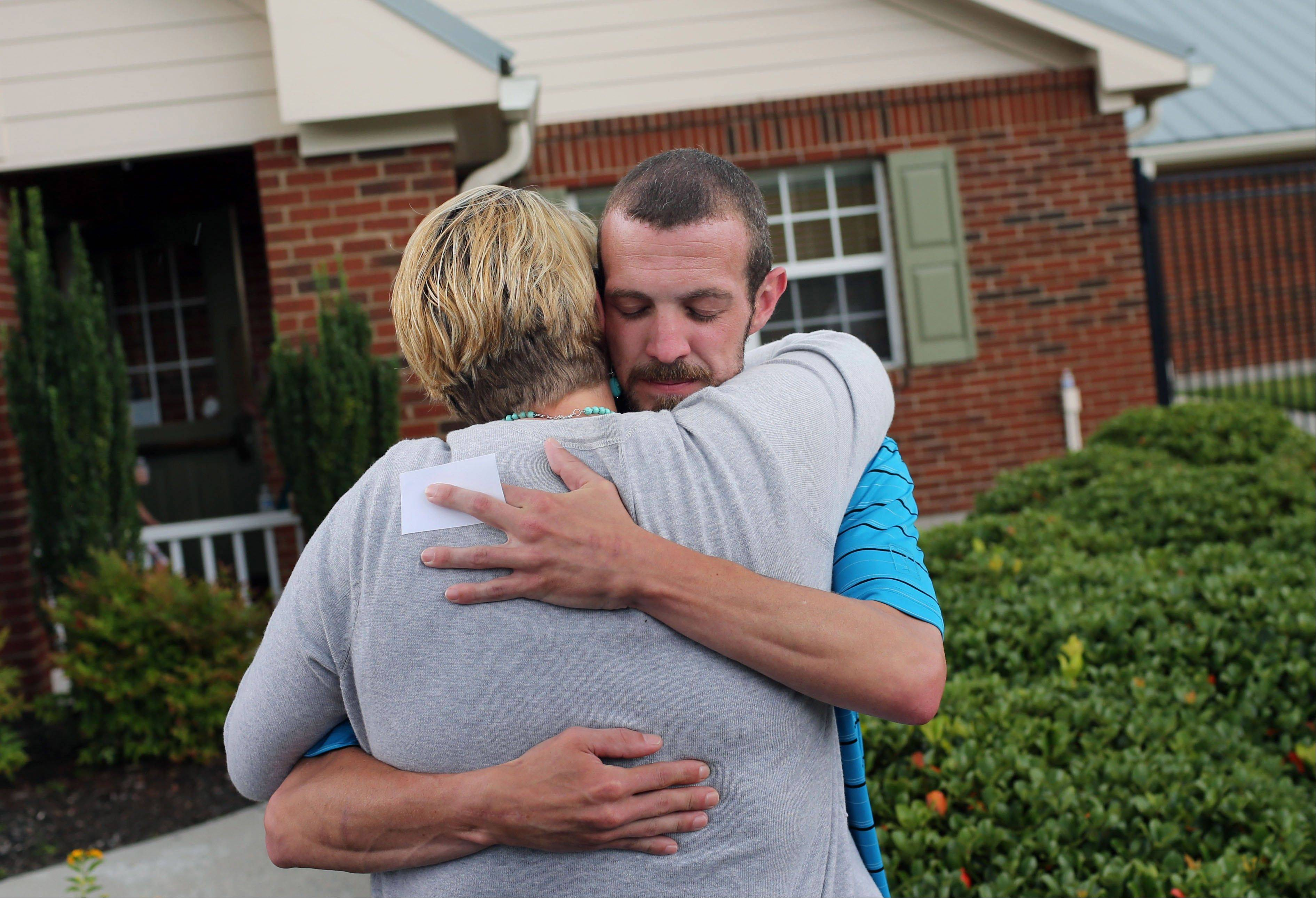 Brendon Mackey's father Bryan Mackey hugs his cousin, Heather Melton, after students of Primrose School of Swift Creek released balloons during a memorial for Brendon in Midlothian, Va.