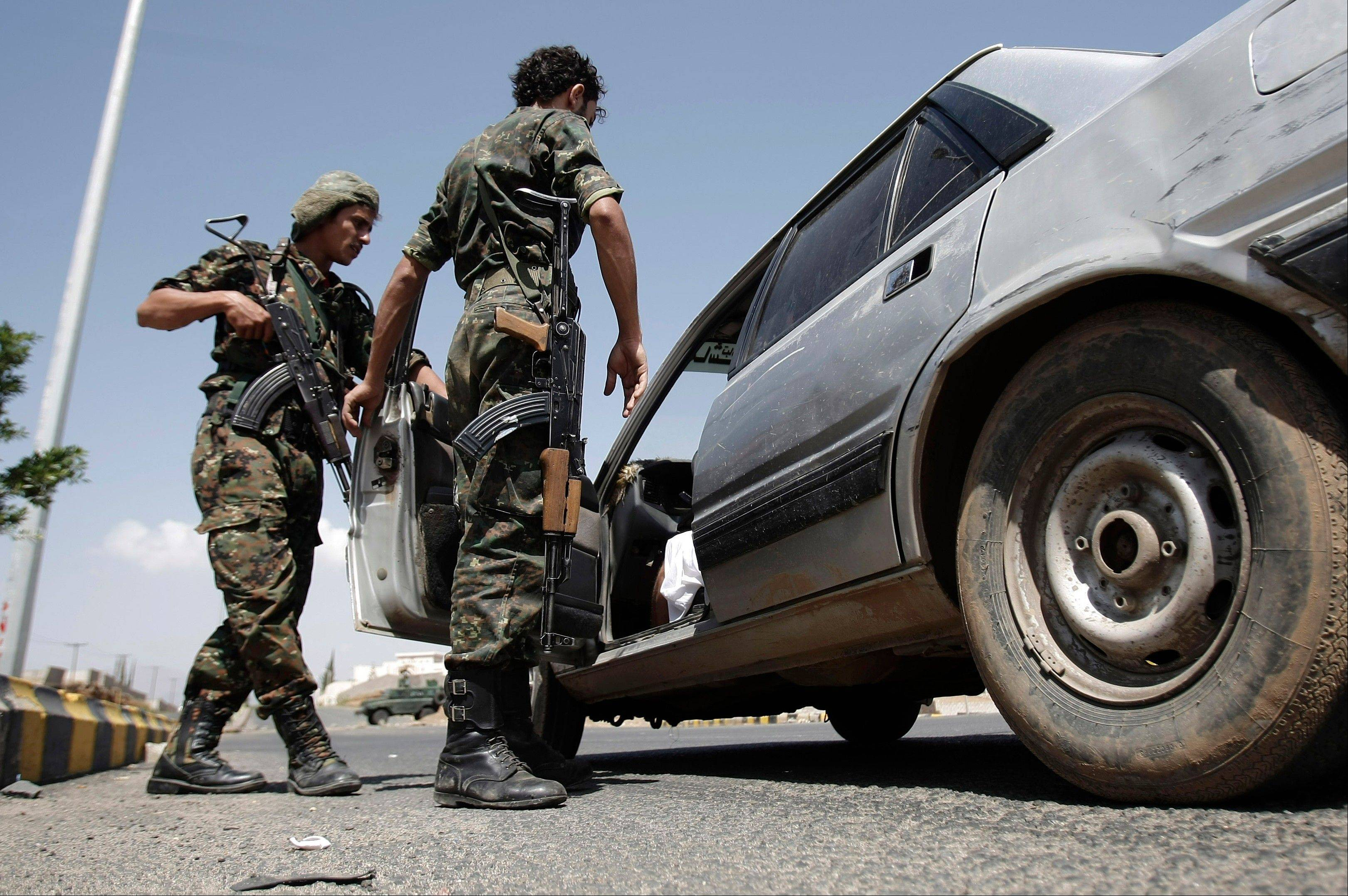 Yemeni soldiers inspect a car at a checkpoint Saturday on a street leading to the U.S. and British embassies in Sanaa, Yemen.