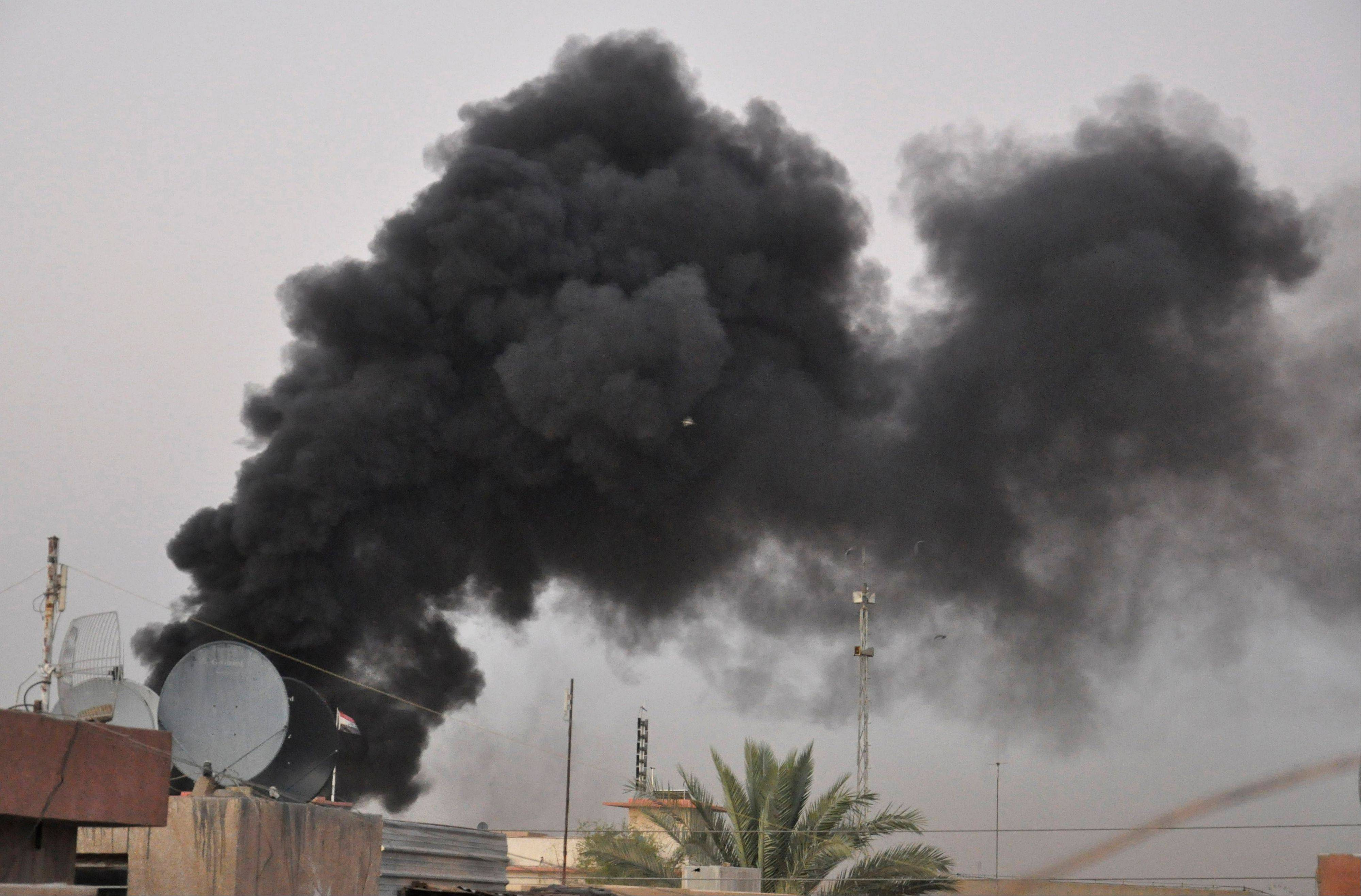 Black smoke from a car bomb attack marks the site Saturday in Baghdad. A wave of car bombings targeted cafes and markets around the Iraqi capital of Baghdad as people celebrate the end of the Muslim holy month of Ramadan, killing and wounding scores of people, officials said.