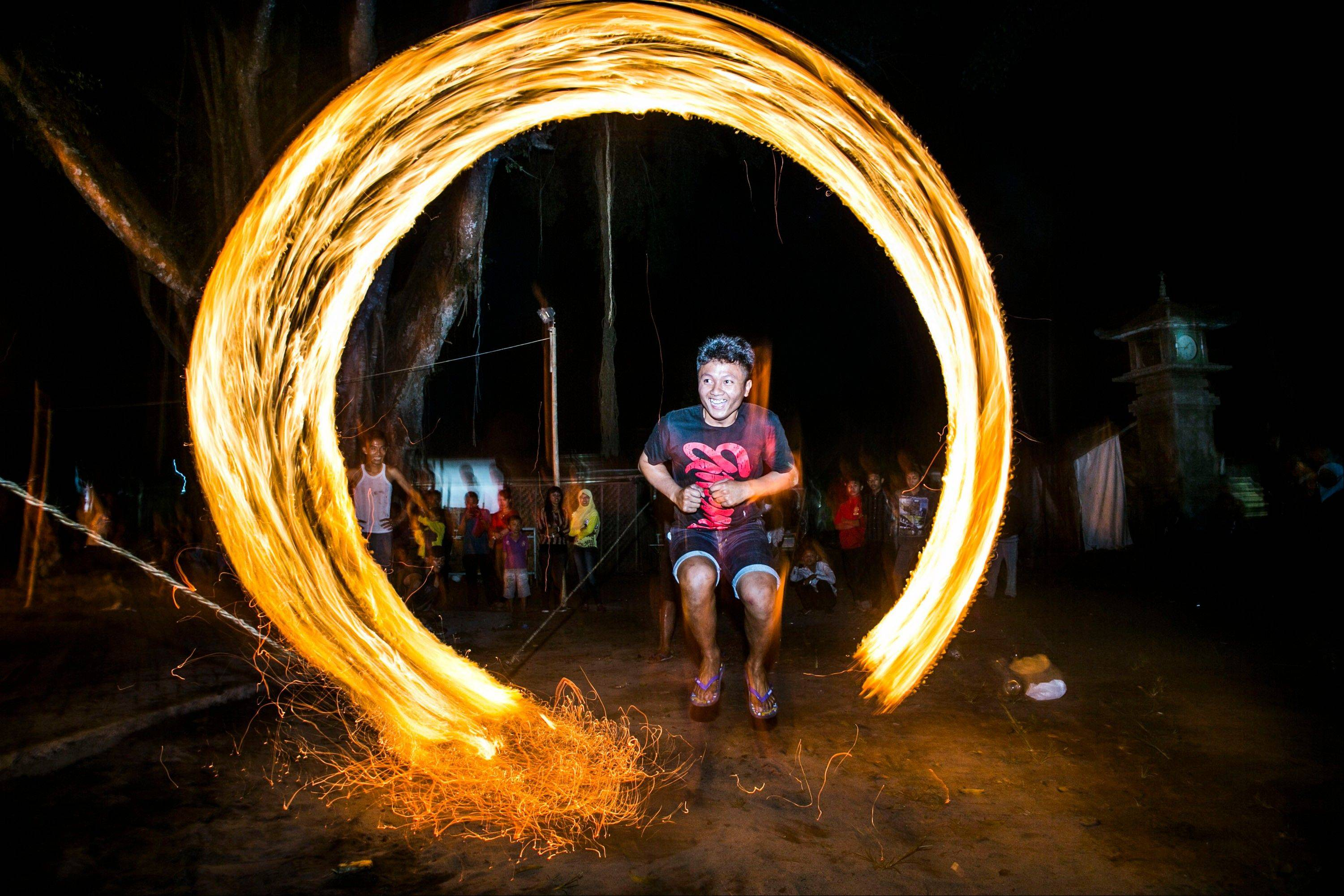 In this photo made with slow shutter speed, an Indonesian youth jumps through flaming rope, during a traditional celebration Thursday marking the end of the holy fasting month of Ramadan.