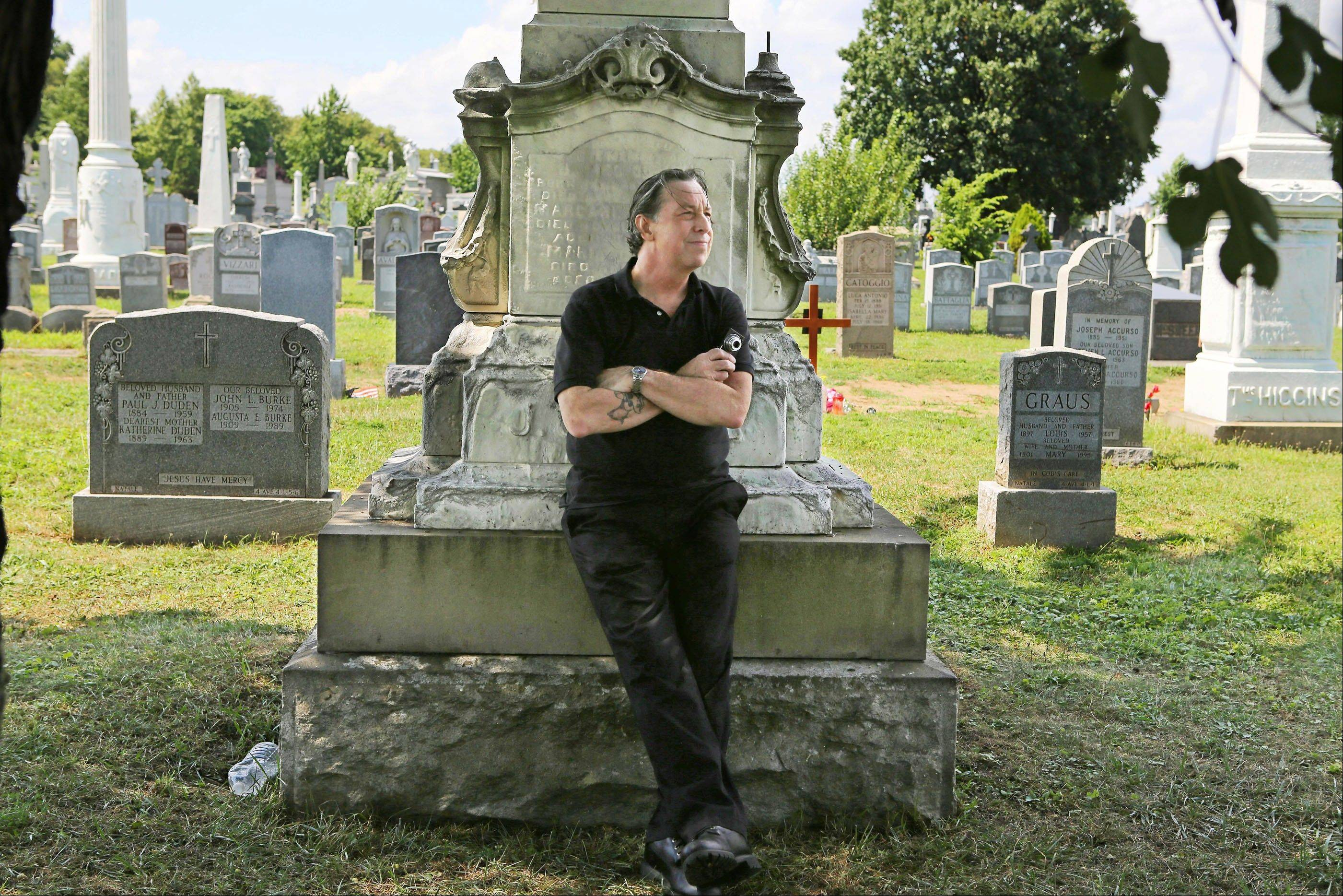 "Patric Abedin, who also goes by the name, ""Nick Beef,"" poses for a photo among the grave markers at Calvary Cemetery in the Queens borough of New York. In 1975 Abedin bought the grave plot next to where presidential assassin Lee Harvey Oswald is buried, and then placed the granite marker inscribed with Nick Beef there in 1997."