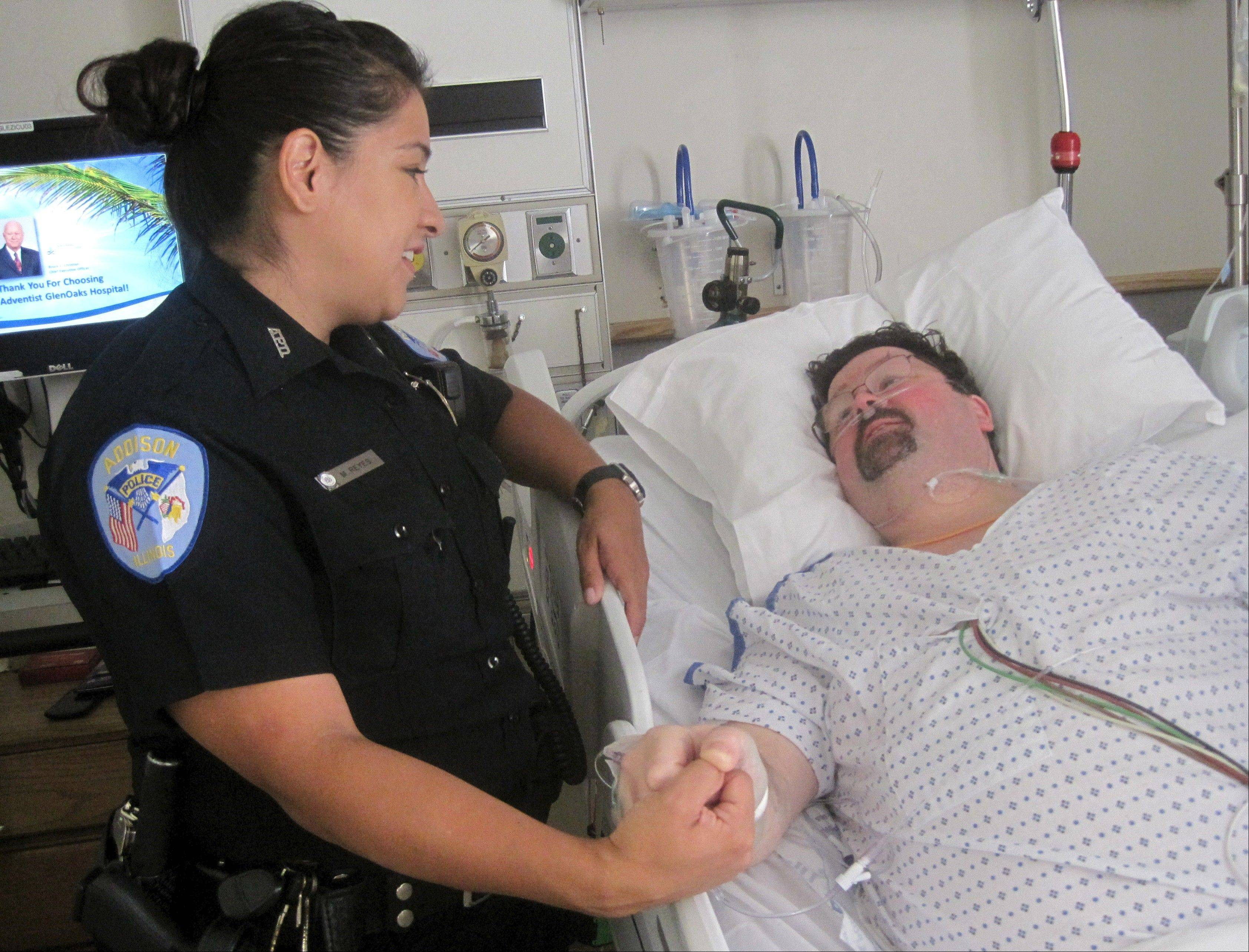 Addison Police Officer Maria Reyes and heart attack victim Ed Sullivan meet for the first time Tuesday during an emotional reunion at Adventist GlenOaks Hospital in Glendale Heights. Sullivan survived after Reyes used an automated external defibrillator to resuscitate him.