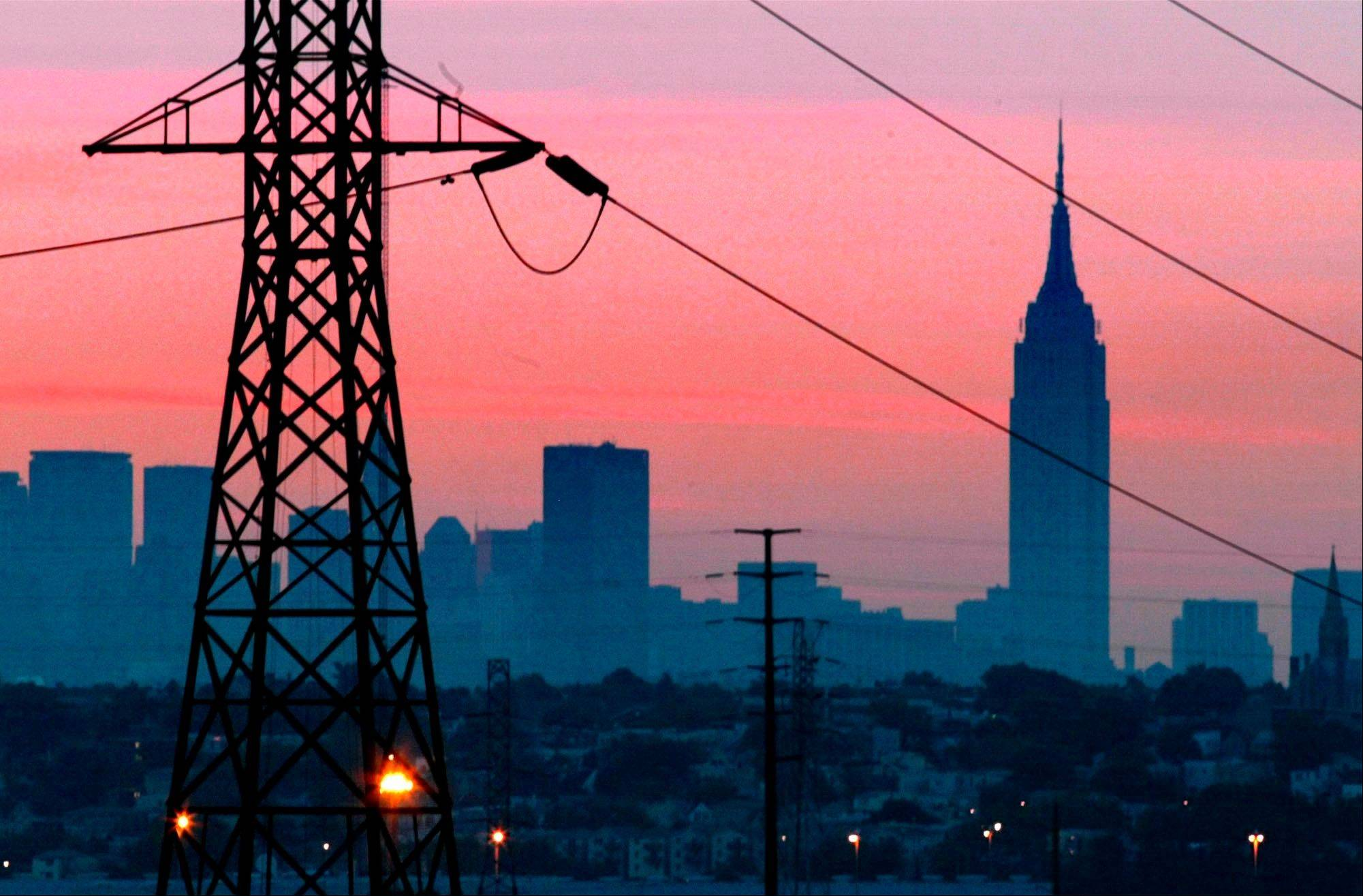 The Empire State Building towers over the skyline of a blackout-darkened New York City just before dawn.