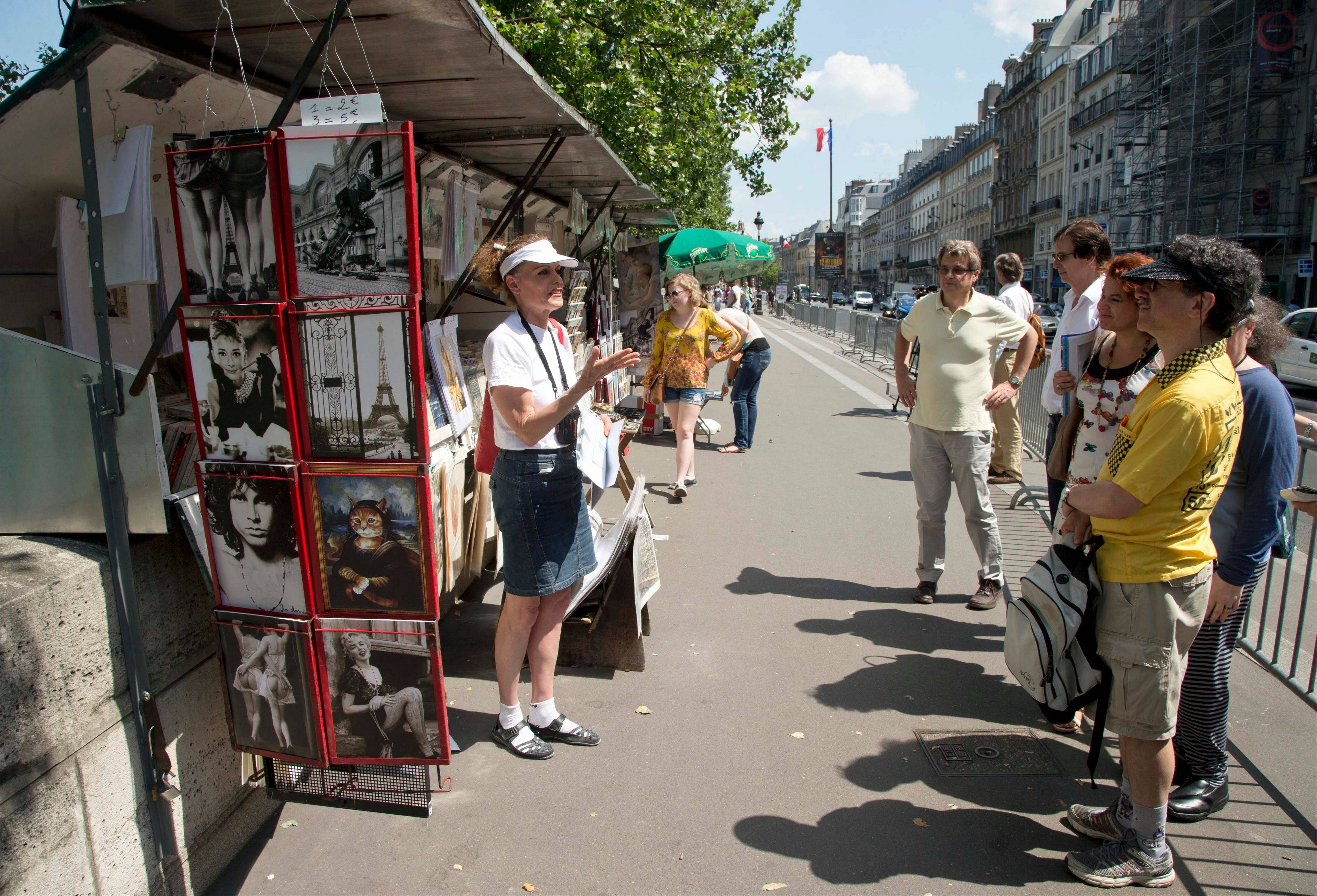 Tour guide Shari Segall, left, speaks about Thomas Jefferson next to a book stand during a tour around the main spots of the Revolutonary-era American presence on Paris' left bank.